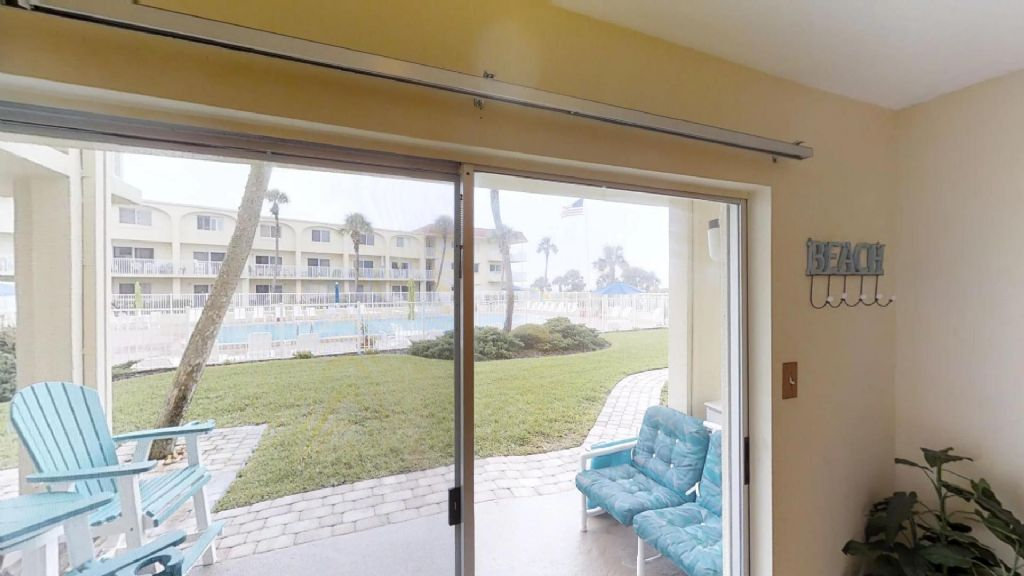 view from living room to pool area and beach