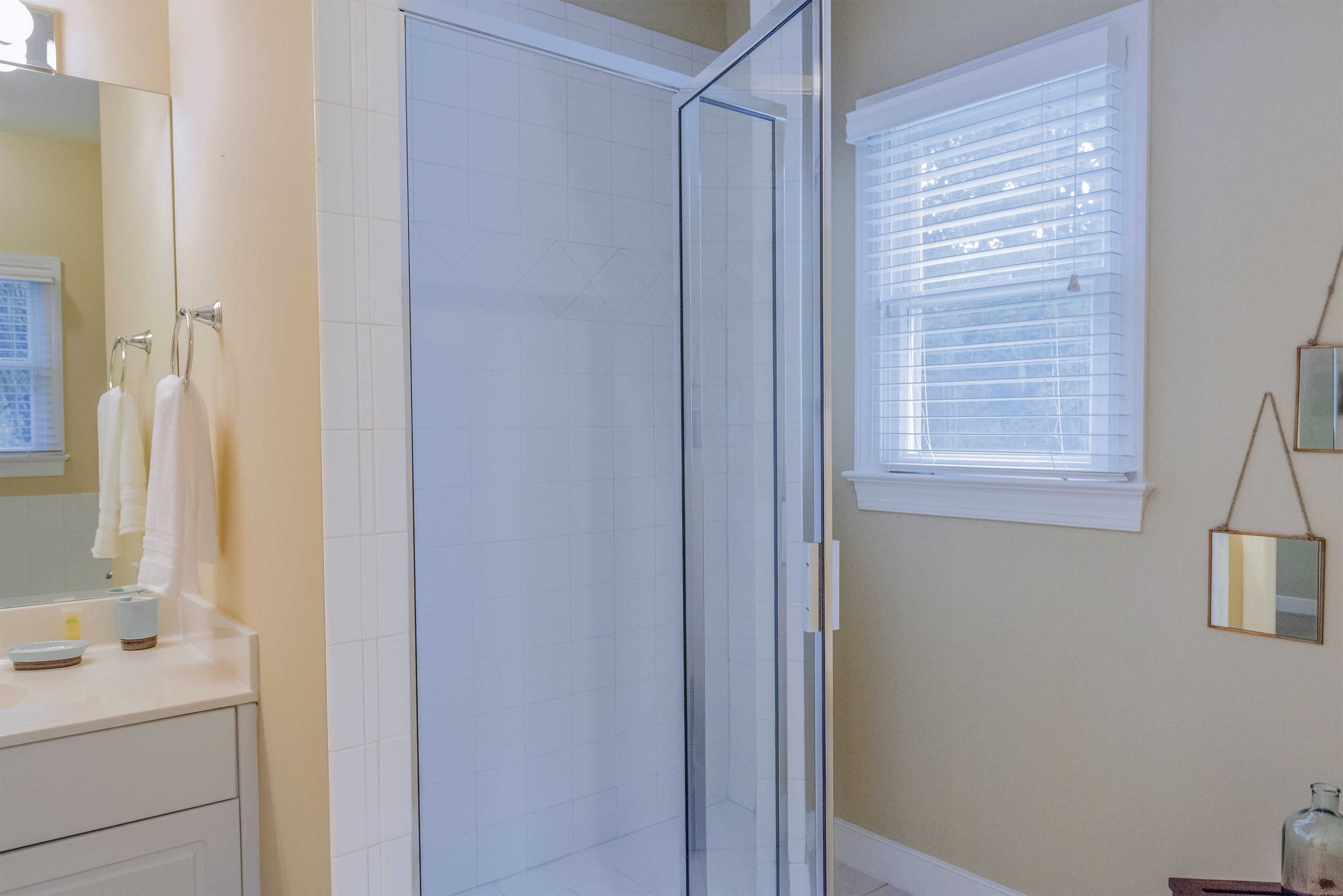 The nearby bathroom has a shower and vanity with granite.