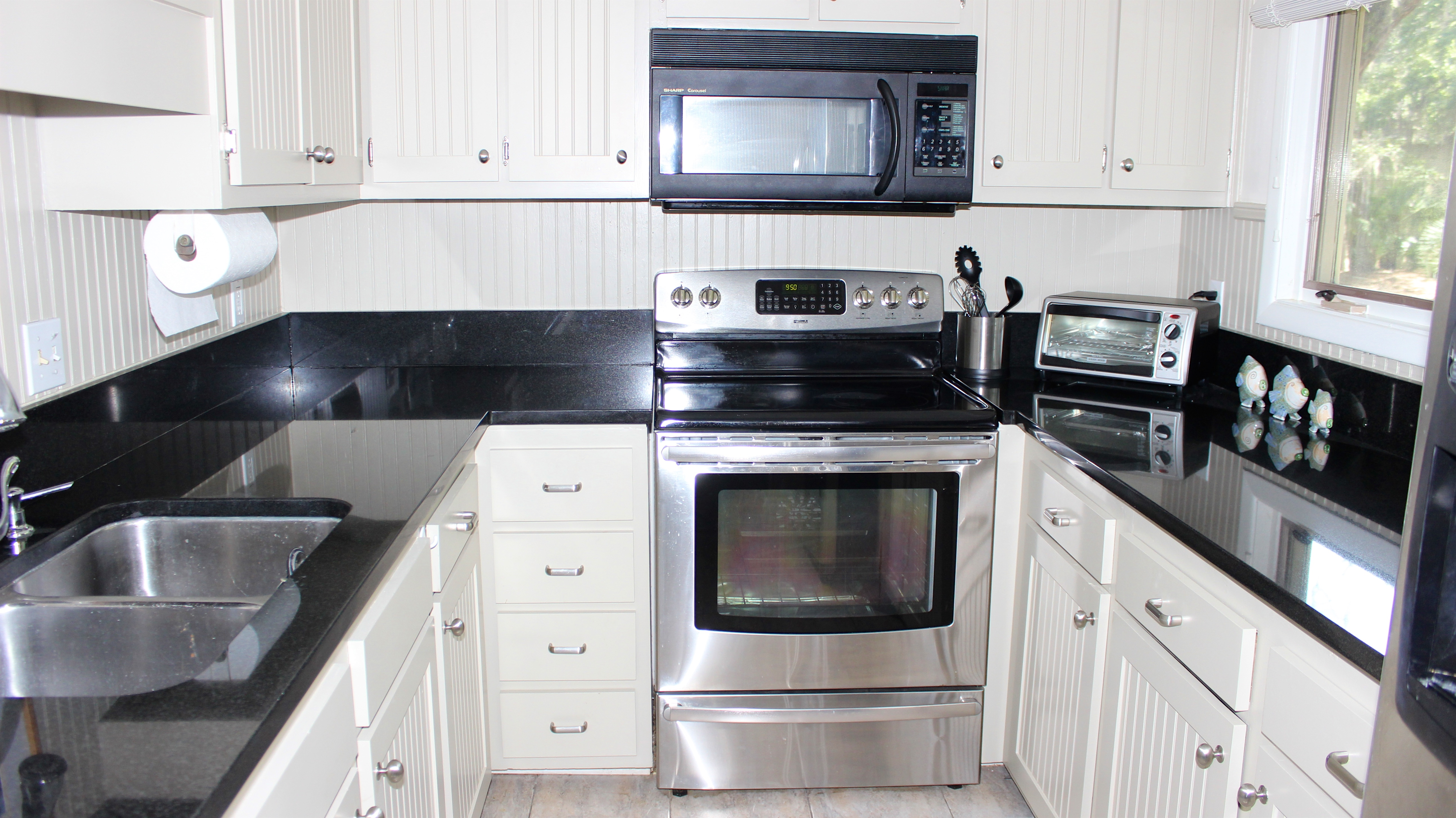 The updated kitchen has dark granite counters and white cabinetry.