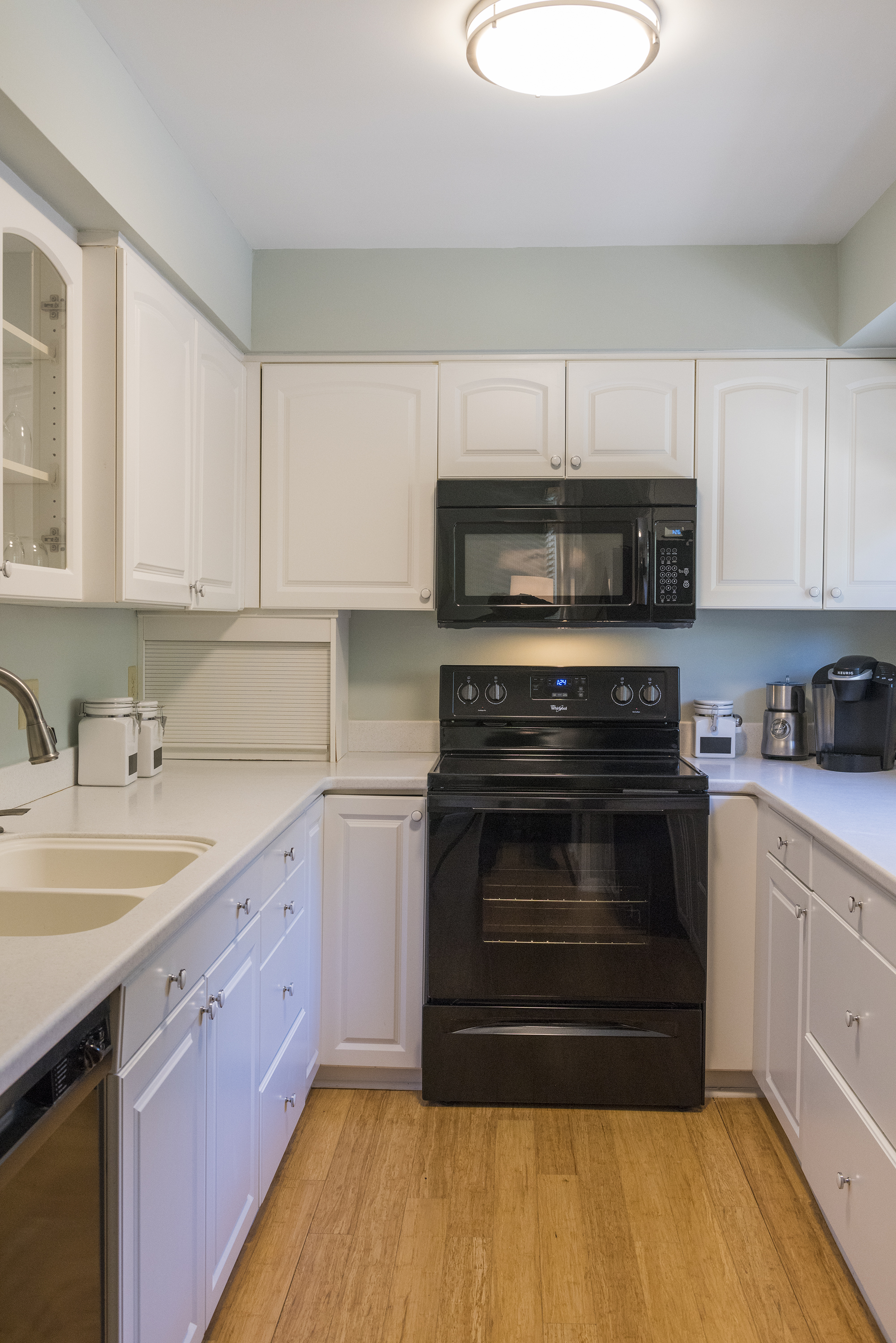 The fully equipped kitchen features Corian counters, Whirpool appliances and a Keurig coffee maker.