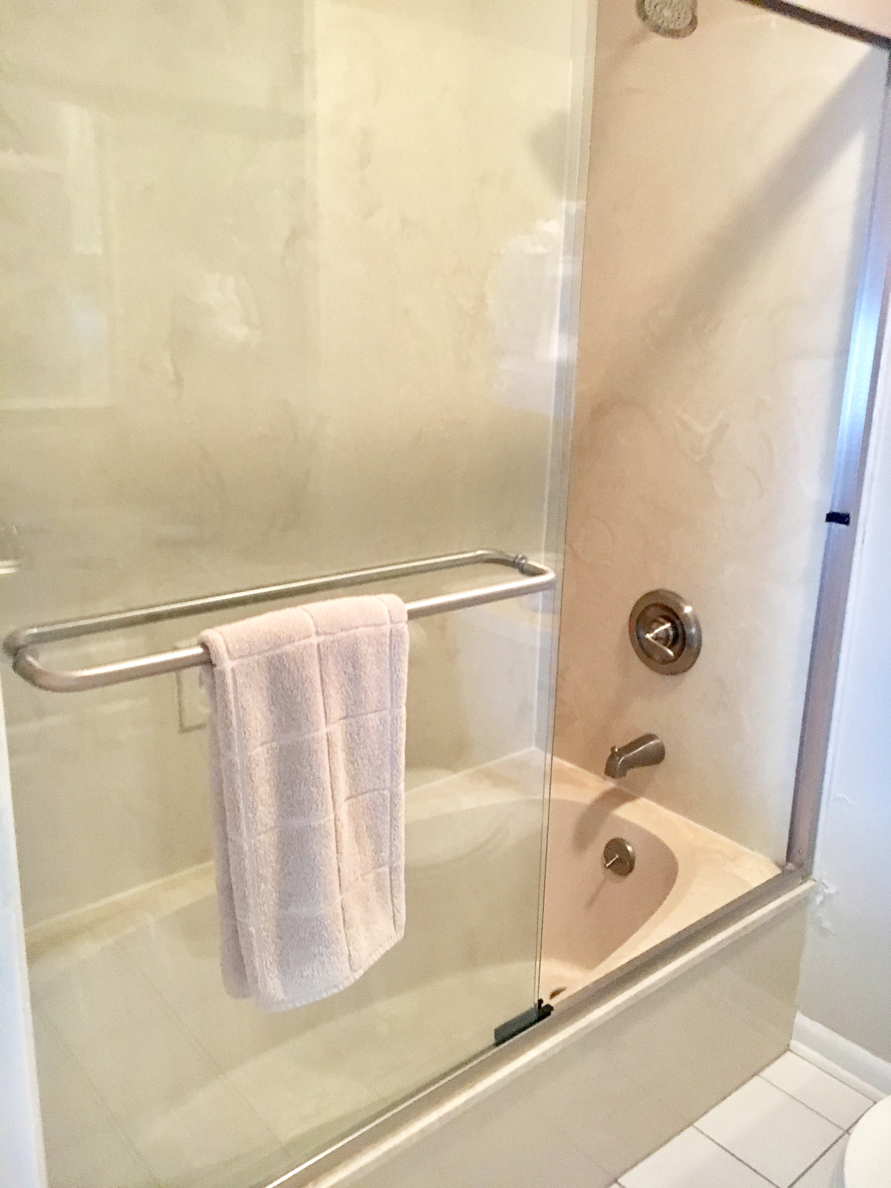It has a tub/shower with a glass sliding door