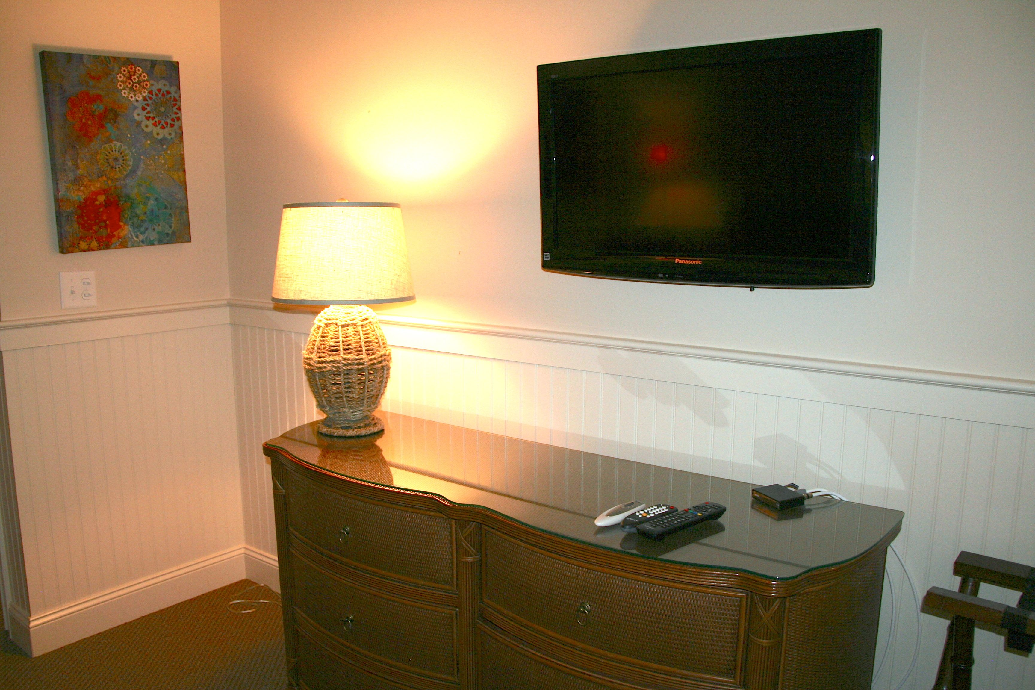 The room has a large HDTV mounted on the wall.