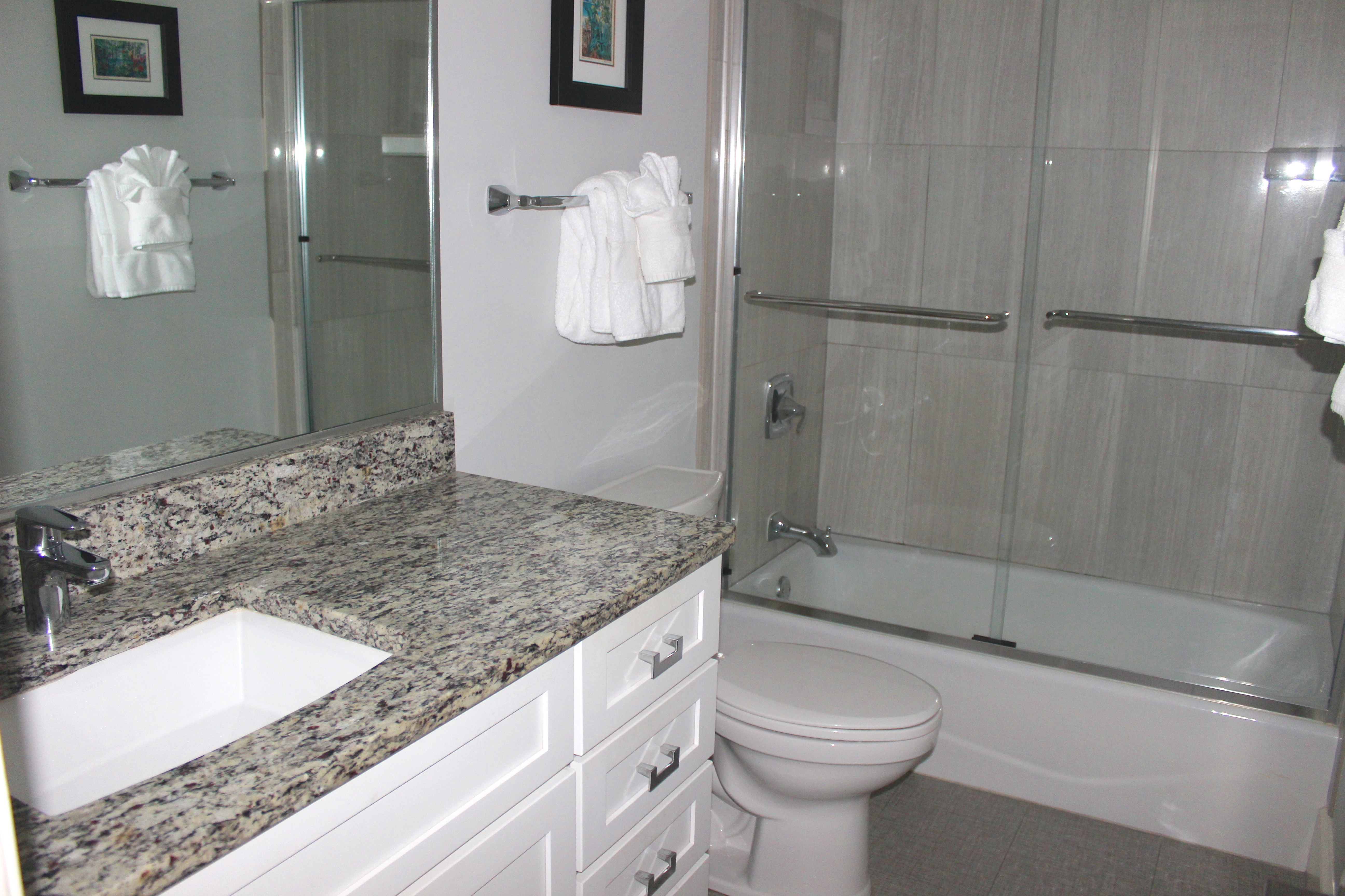 The en suite bath has a tiled tub/shower and large granite topped vanity.