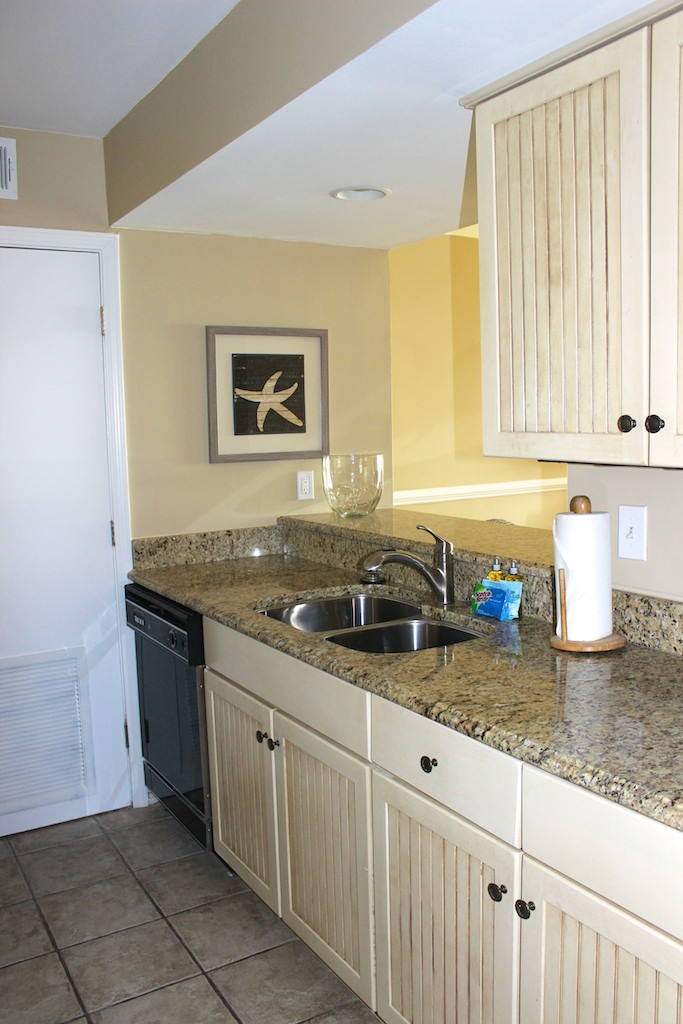 The kitchen has granite countertops and well stocked wainscot cabinets.