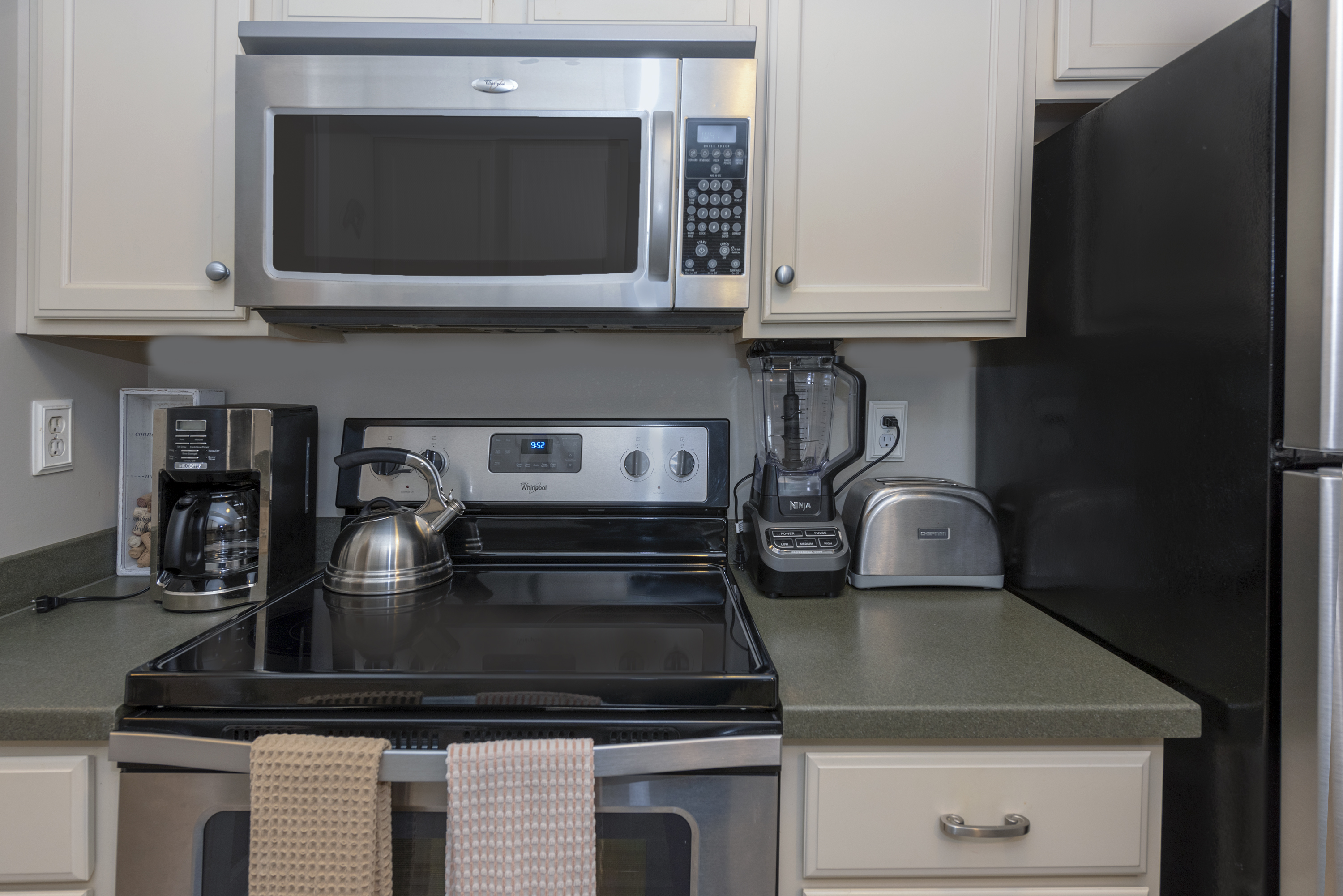 The fully equipped kitchen has granite countertops and white cabinetry.
