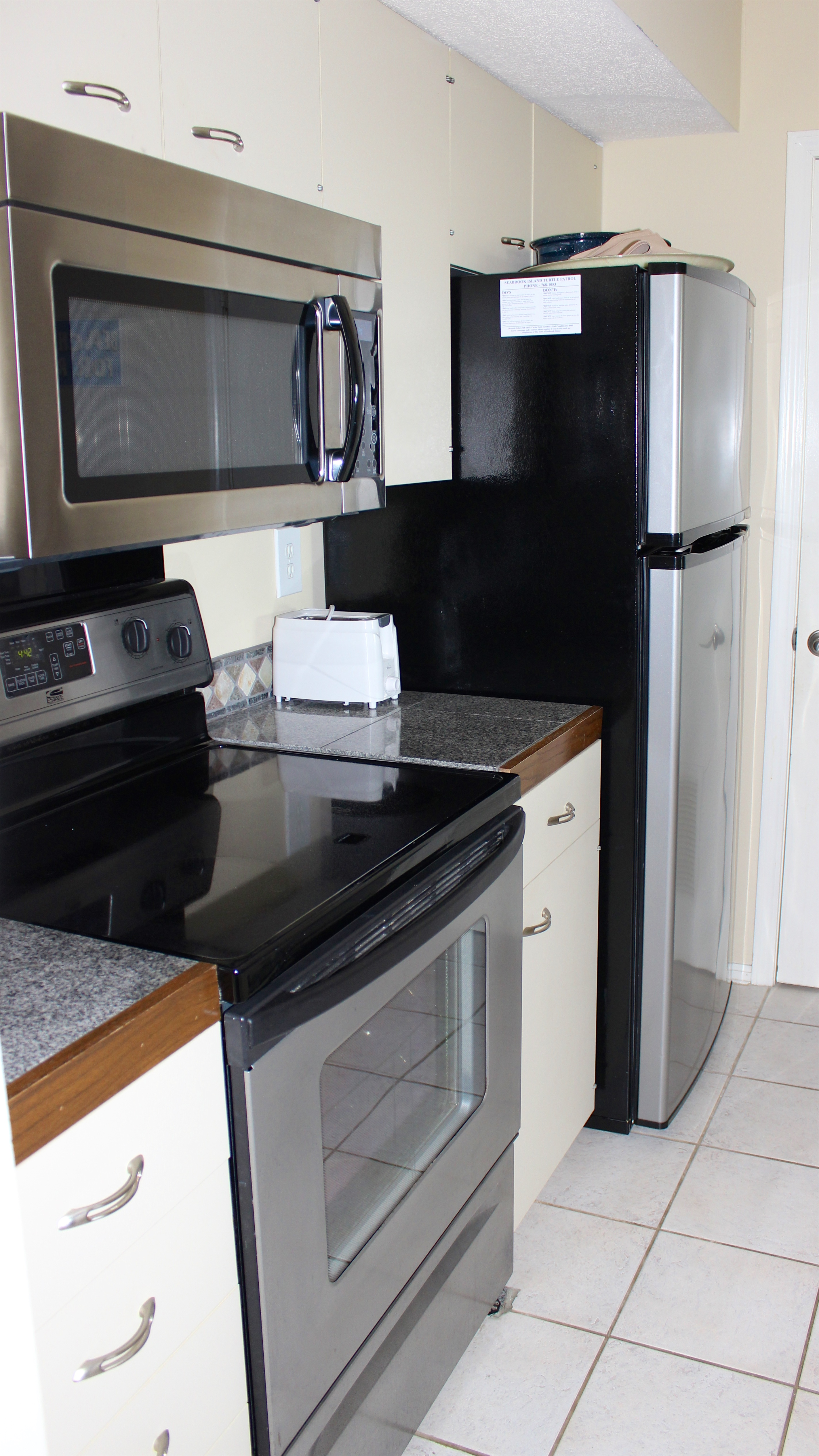 The kitchen has tile counters and stainless appliances.