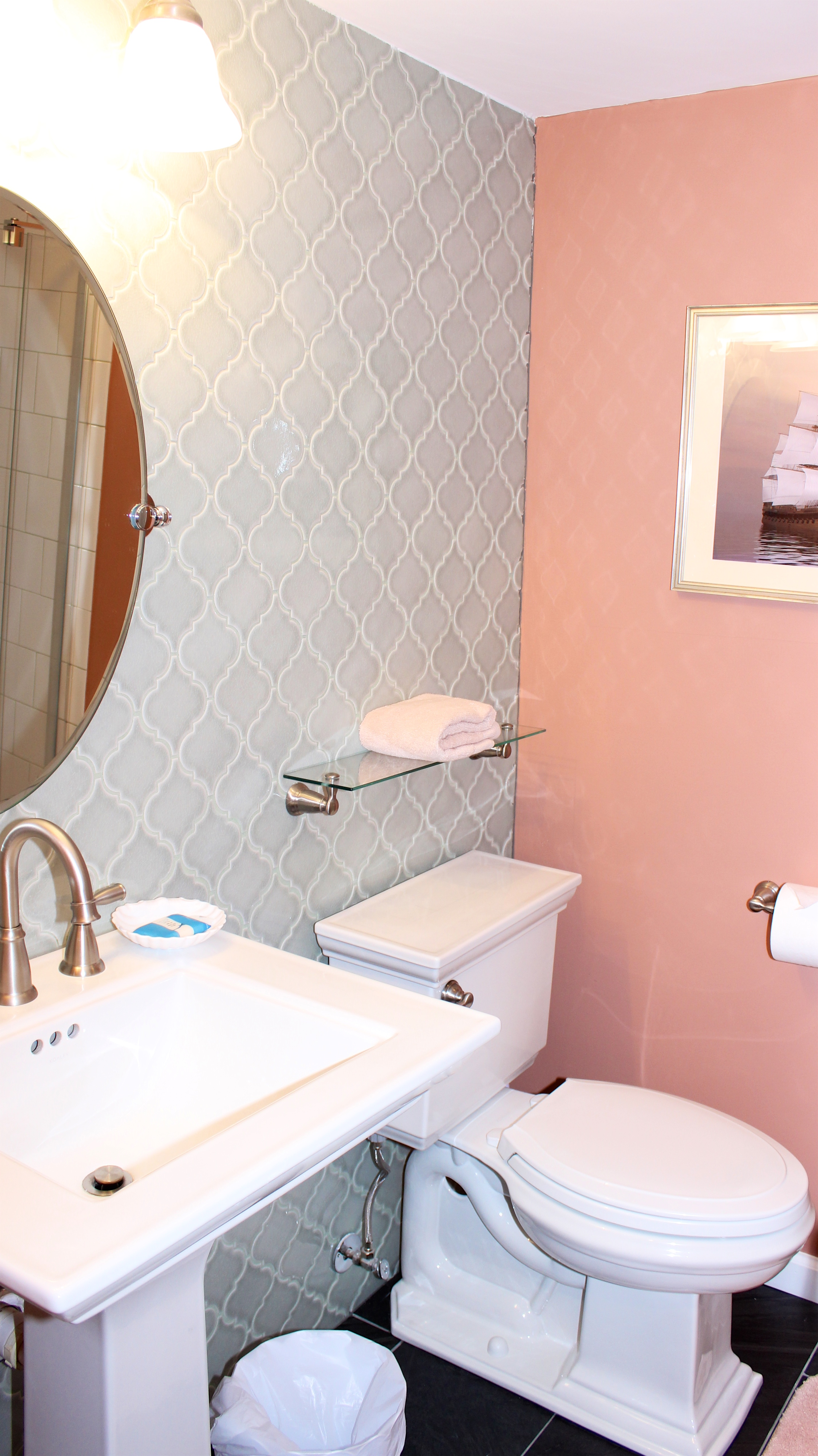 Off the hall is a full bath. It features a tile wall and pedestal sink.