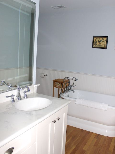 This large bathroom features a large vanity and a soaking tub.