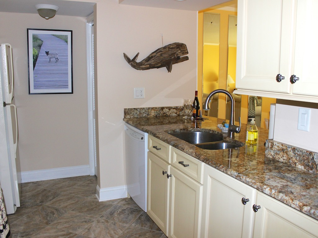 The kitchen has tile flooring, a double sink, and views to the river beyond.