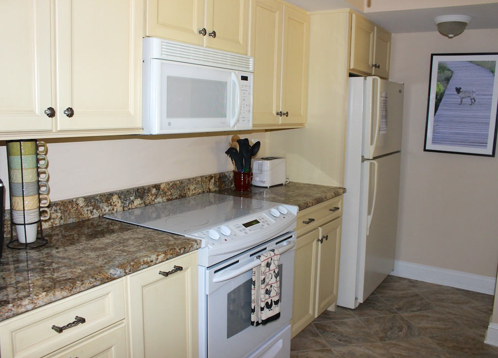 The roomy kitchen has custom cabinets, granite counters and extended space.