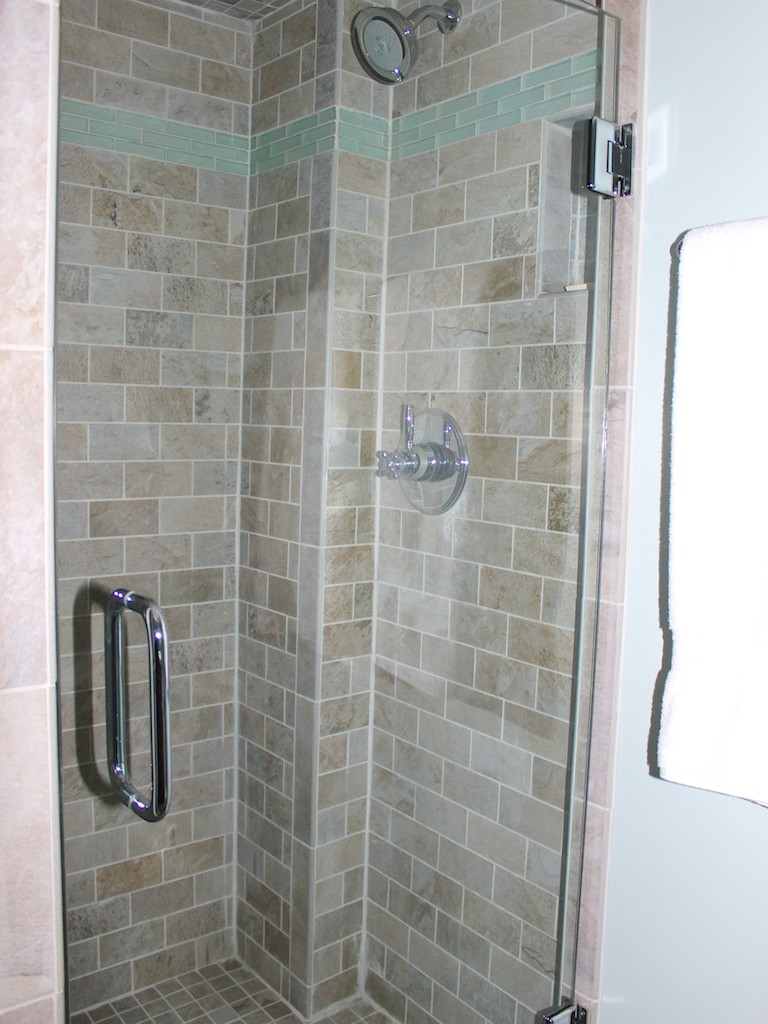 The shower has a beautiful tan subway tile and a glass door.