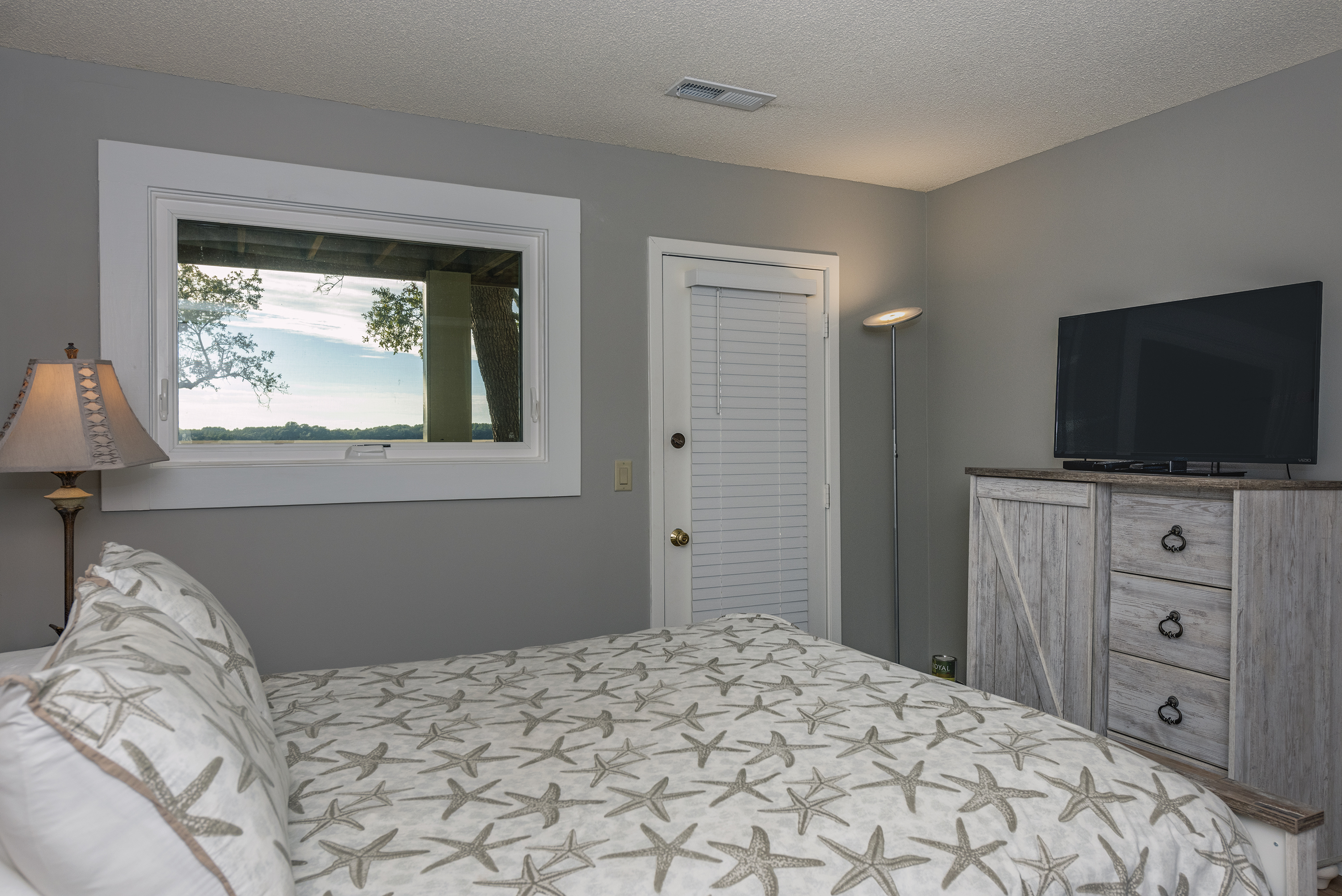 TV for viewing and private deck that has a beautiful marsh view.