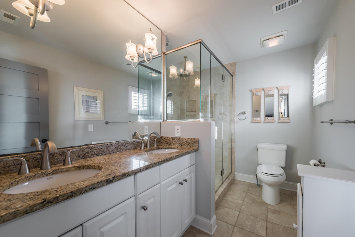 The master bathroom has tile flooring, granite counters and a tiled walk-in shower.