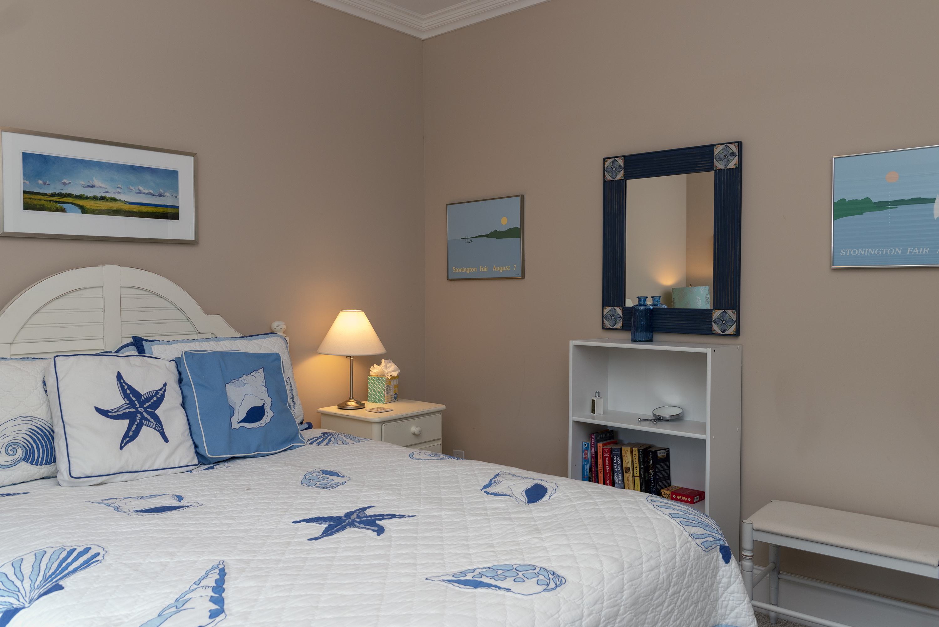 """The guest bedroom has a """"beachy"""" decor with a comfortable bed."""