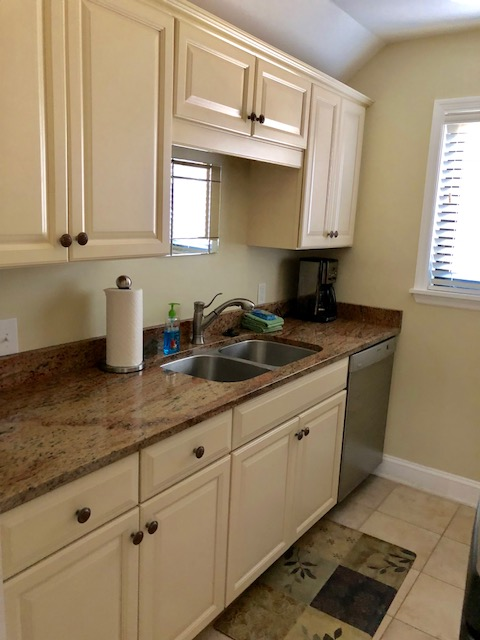 Galley kitchen with granite countertops, fully stocked with utensils.