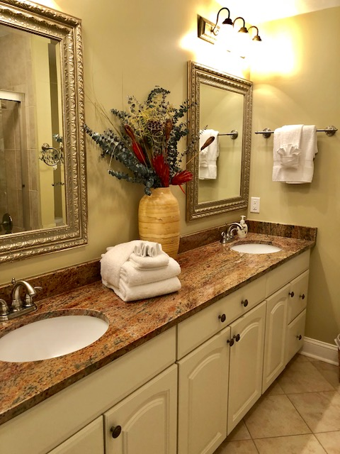A granite topped, double sink vanity provides lots of counter and storage space.