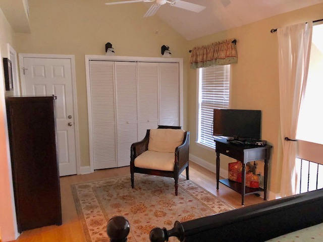The spacious bedroom offers a convenient dressing/sitting area and large closet.