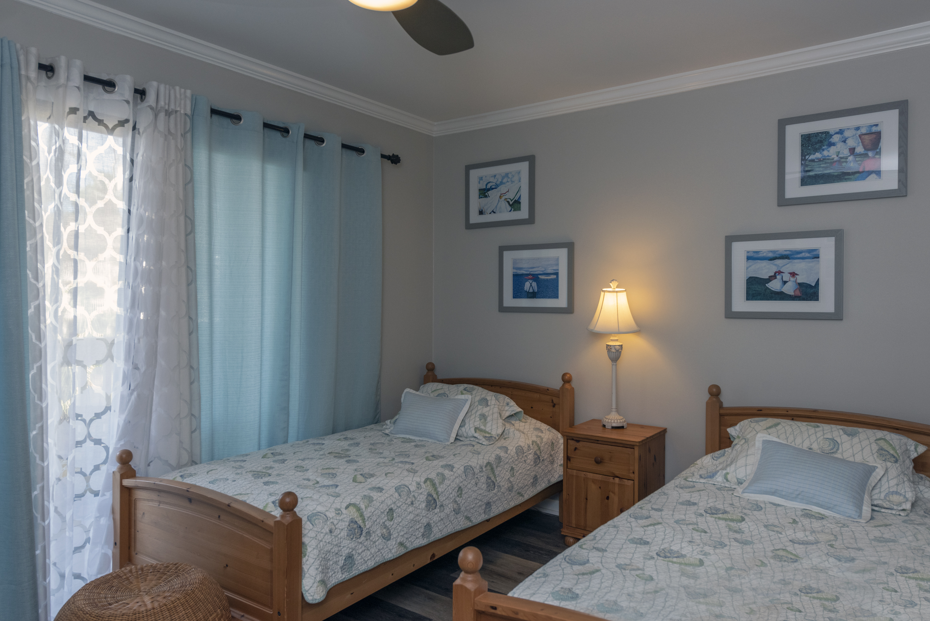 Guest bedroom has two twin beds with an attached full bathroom and tub/shower combination.