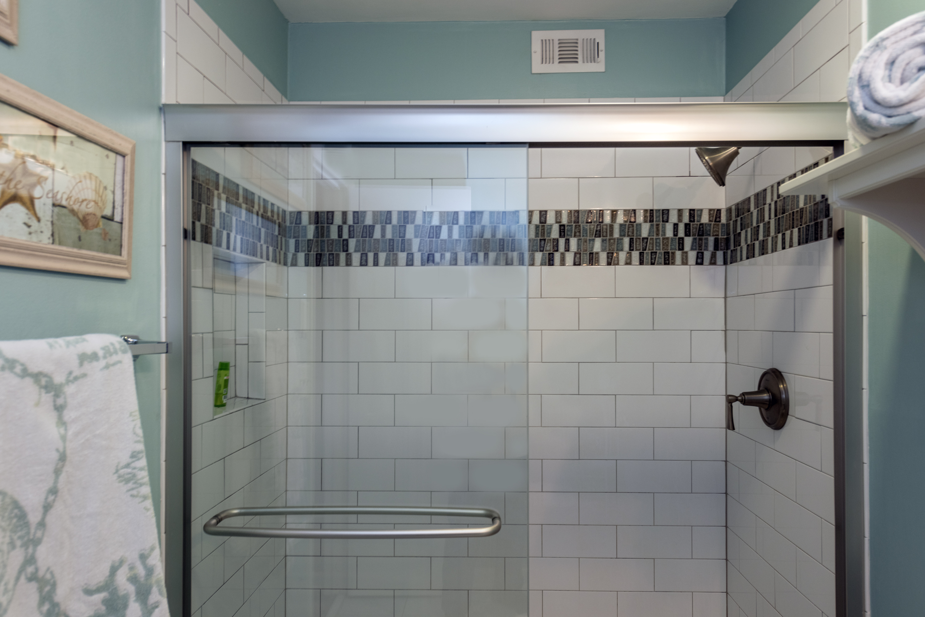 The large tiled shower has plenty of room  and glass doors.