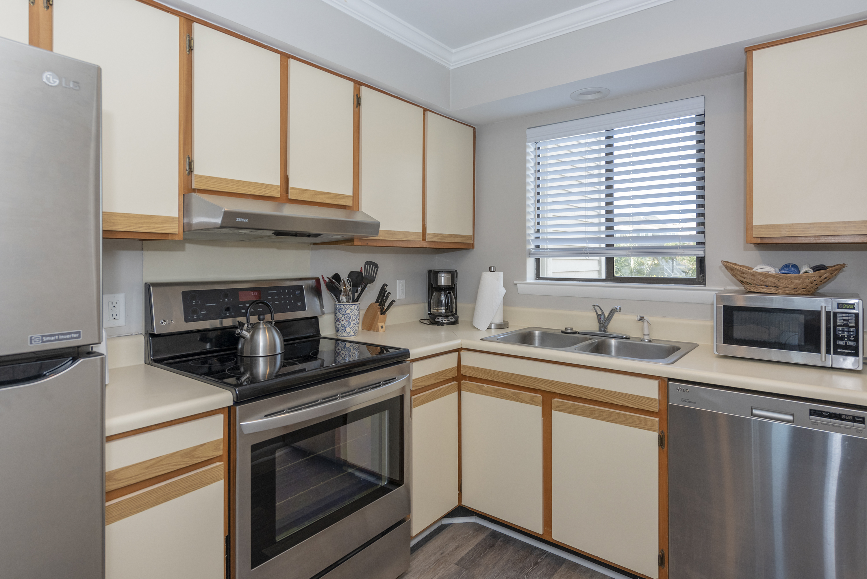 Open kitchen has stainless appliances and is well stocked.