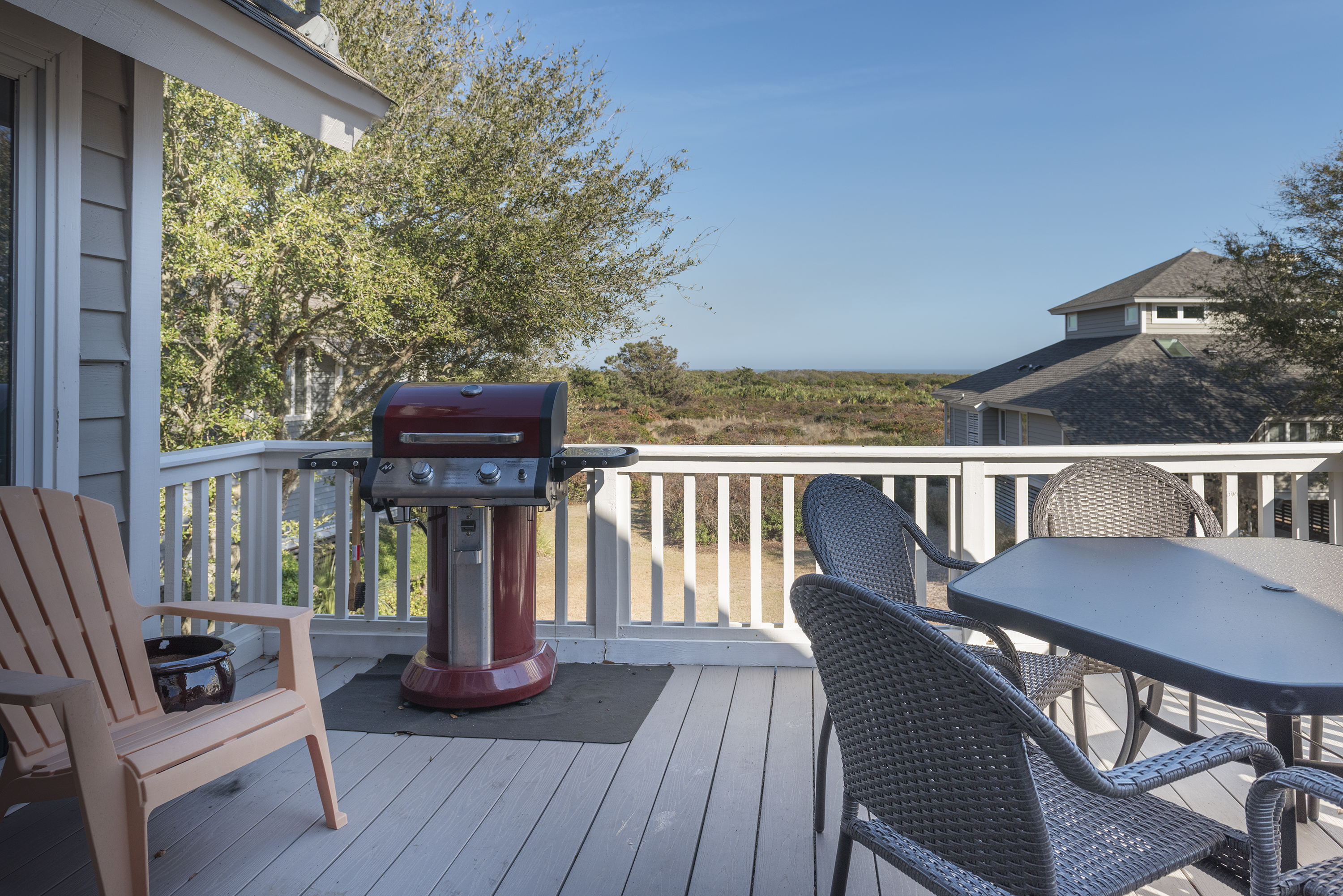 The deck has a gas grill, Adirondack chairs, and a dining table for 6.