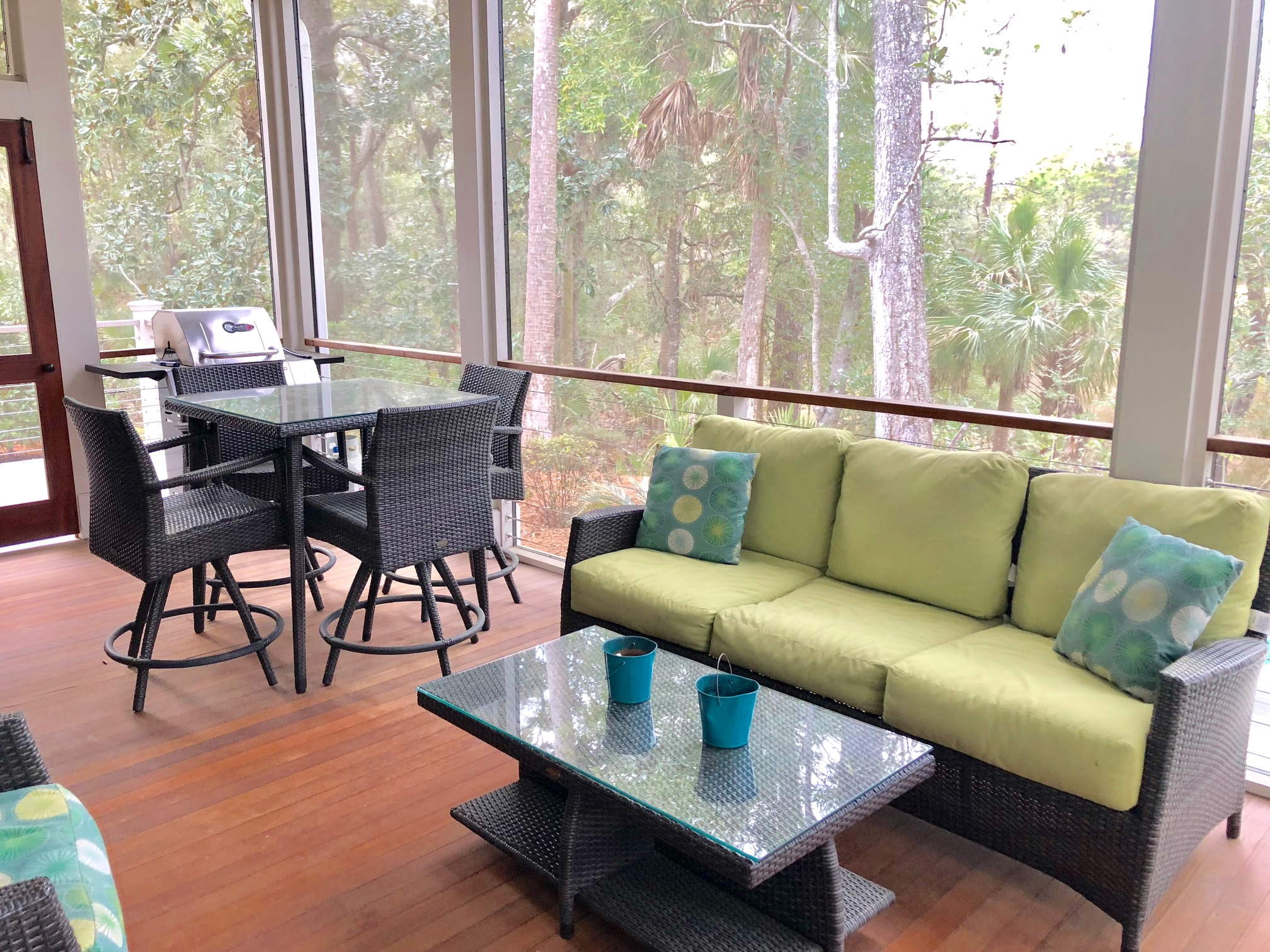Access the screen porch from the great room.  There is ample space for relaxing and dining.  The screen porch also houses a gas grill.