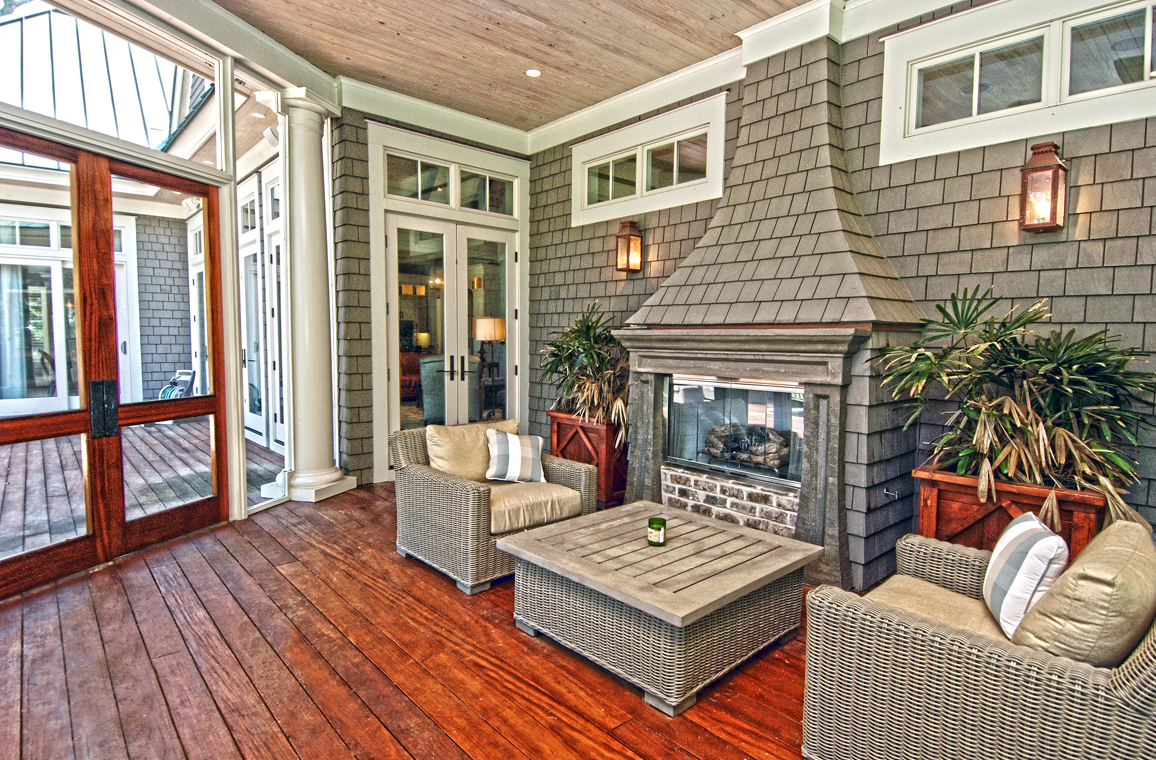 The large screened porch has a gas fireplace and dining table.