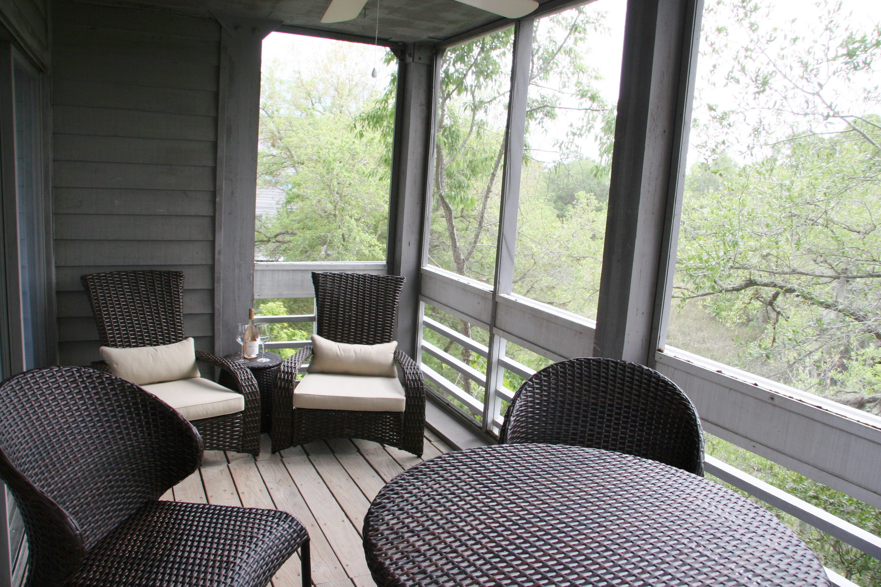 New furniture on the screened in porch off the living area.