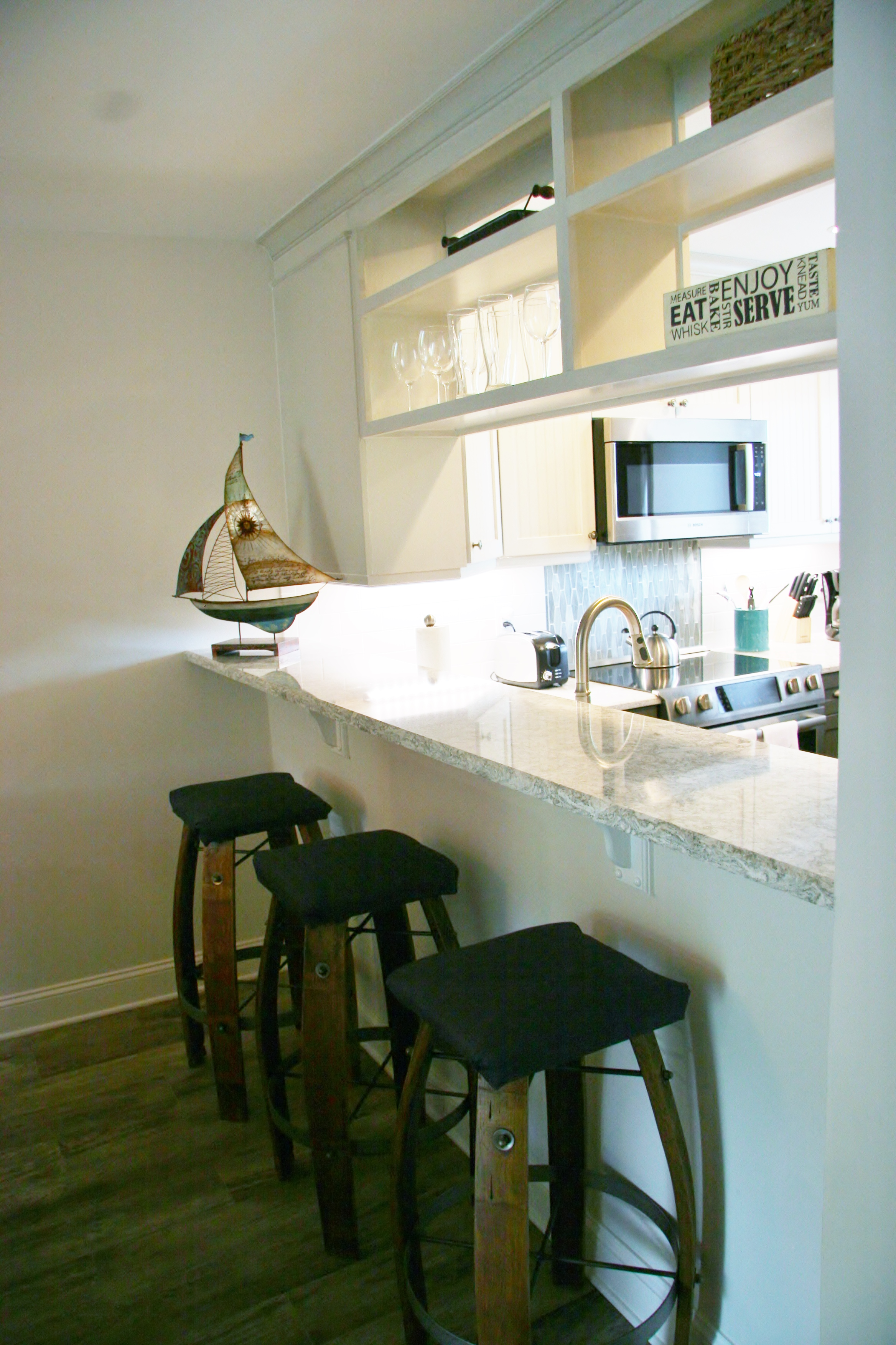 Sit on the bar stools while watching ones in the kitchen.