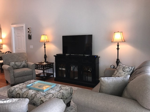 There is a large screen HDTV/DVD in the living room. The living room has a ceiling fan and the remote for the fan is in a basket on the side table to the left.