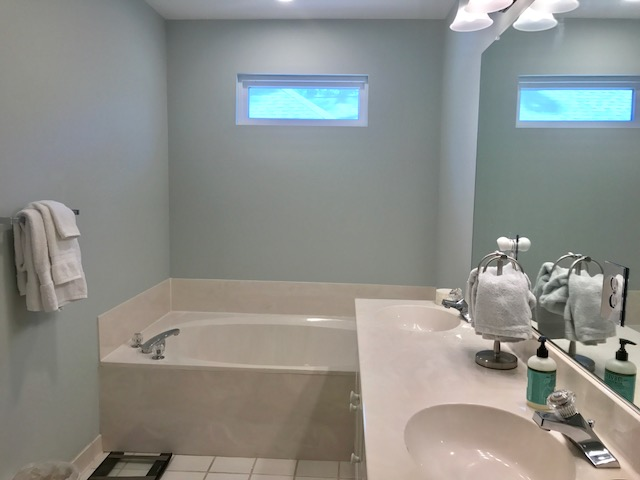 The master has an en suite bathroom with a jetted tub and two sinks.