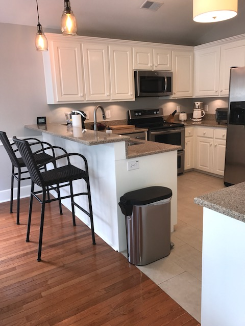 Pretty white cabinets, granite counter tops and pendant lights adorn this kitchen. There is a keurig coffee pot and a toaster oven for your use.