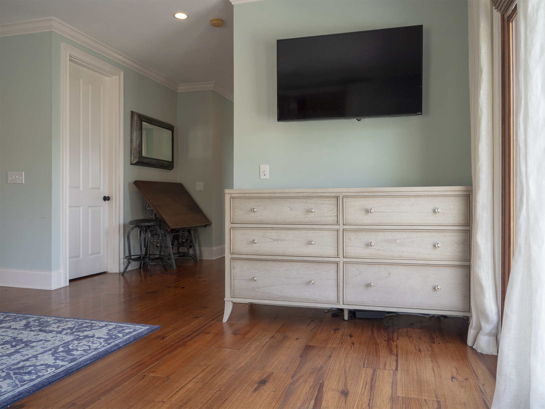 Dresser storage and wall mounted HDTV in master bedroom