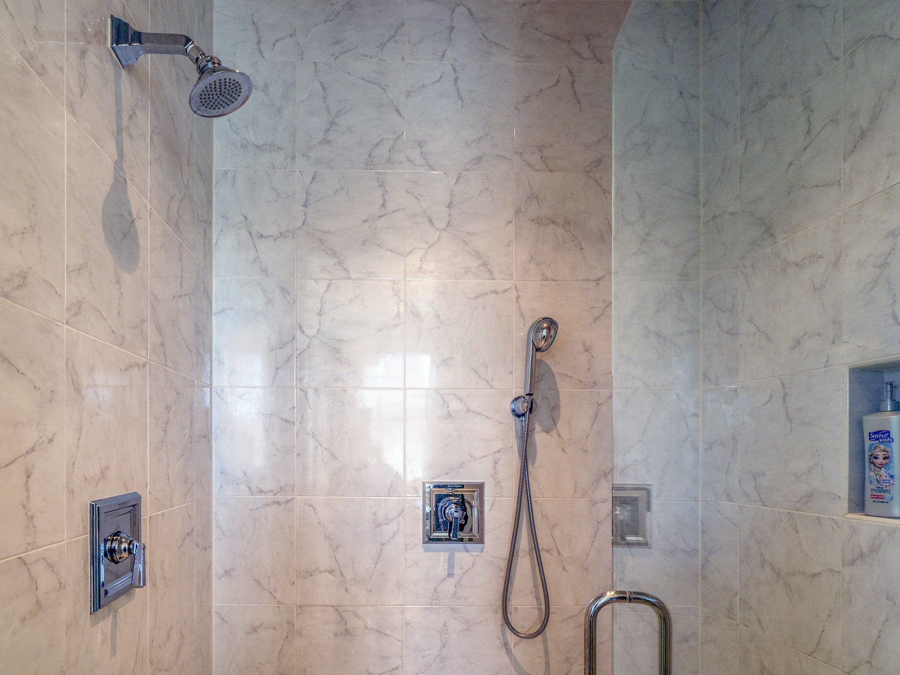 Large tiled shower with additional hand held shower.