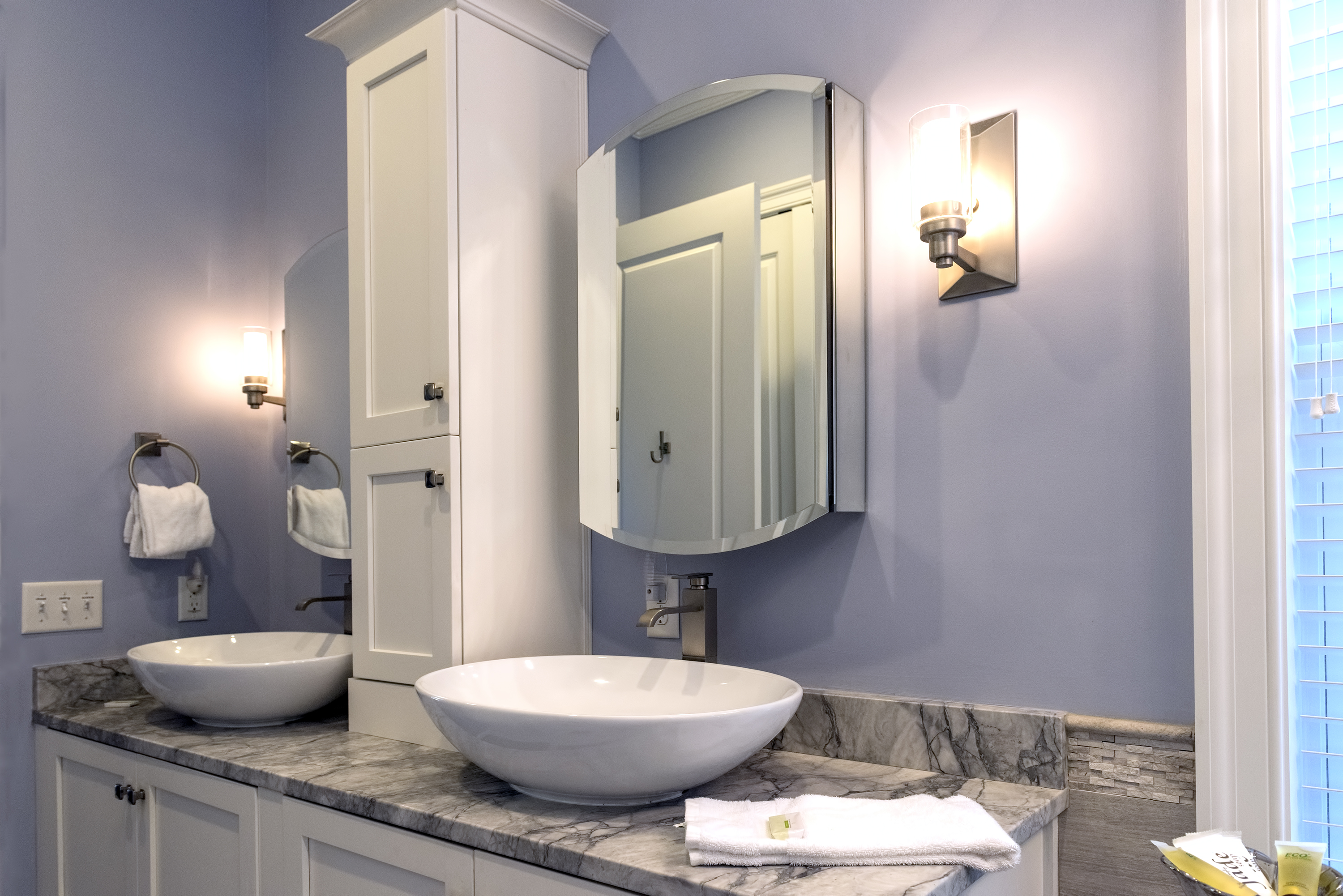 The vanity has two vessel sinks. Just beyond is the large master closet.