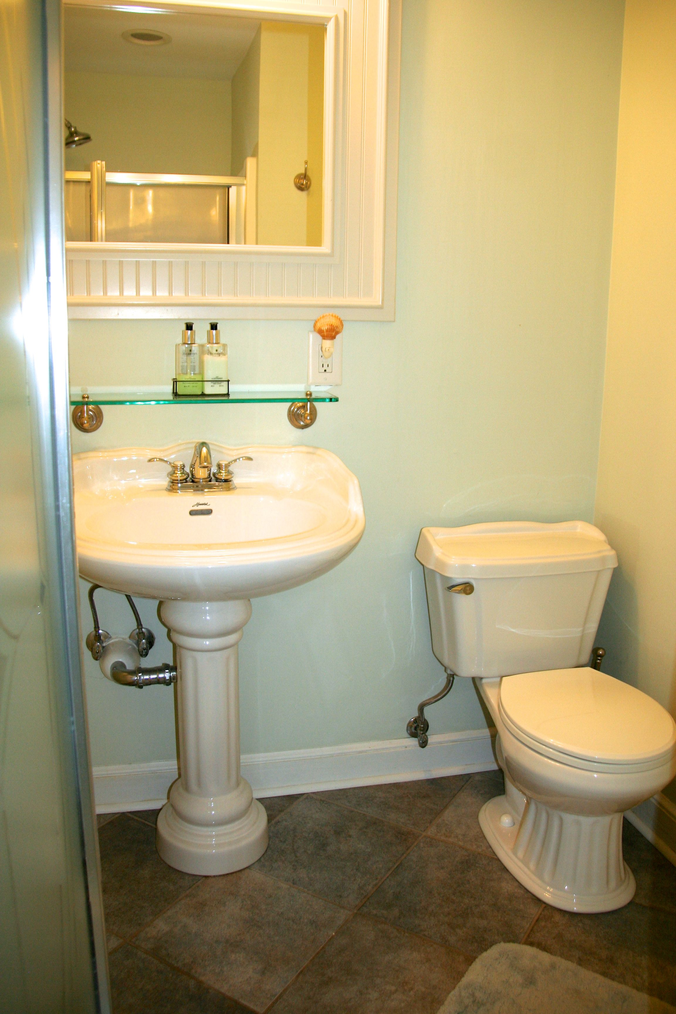 The bathroom has a tile flooring, a pedestal sink, and shower.