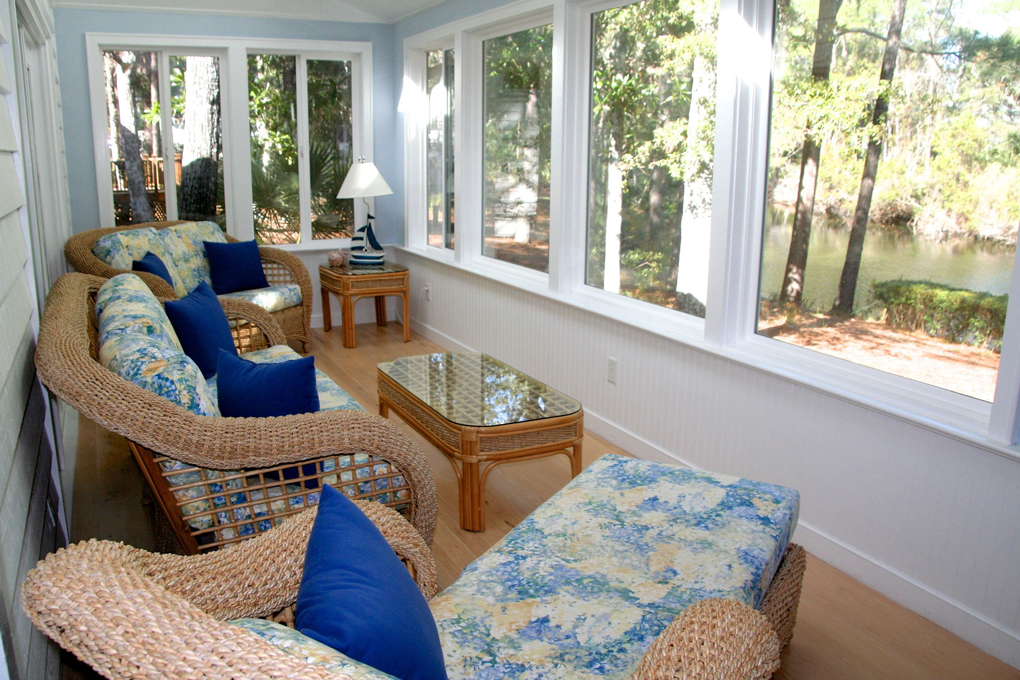 Sliding doors open into the amazing sunroom with panoramic views of a lagoon.