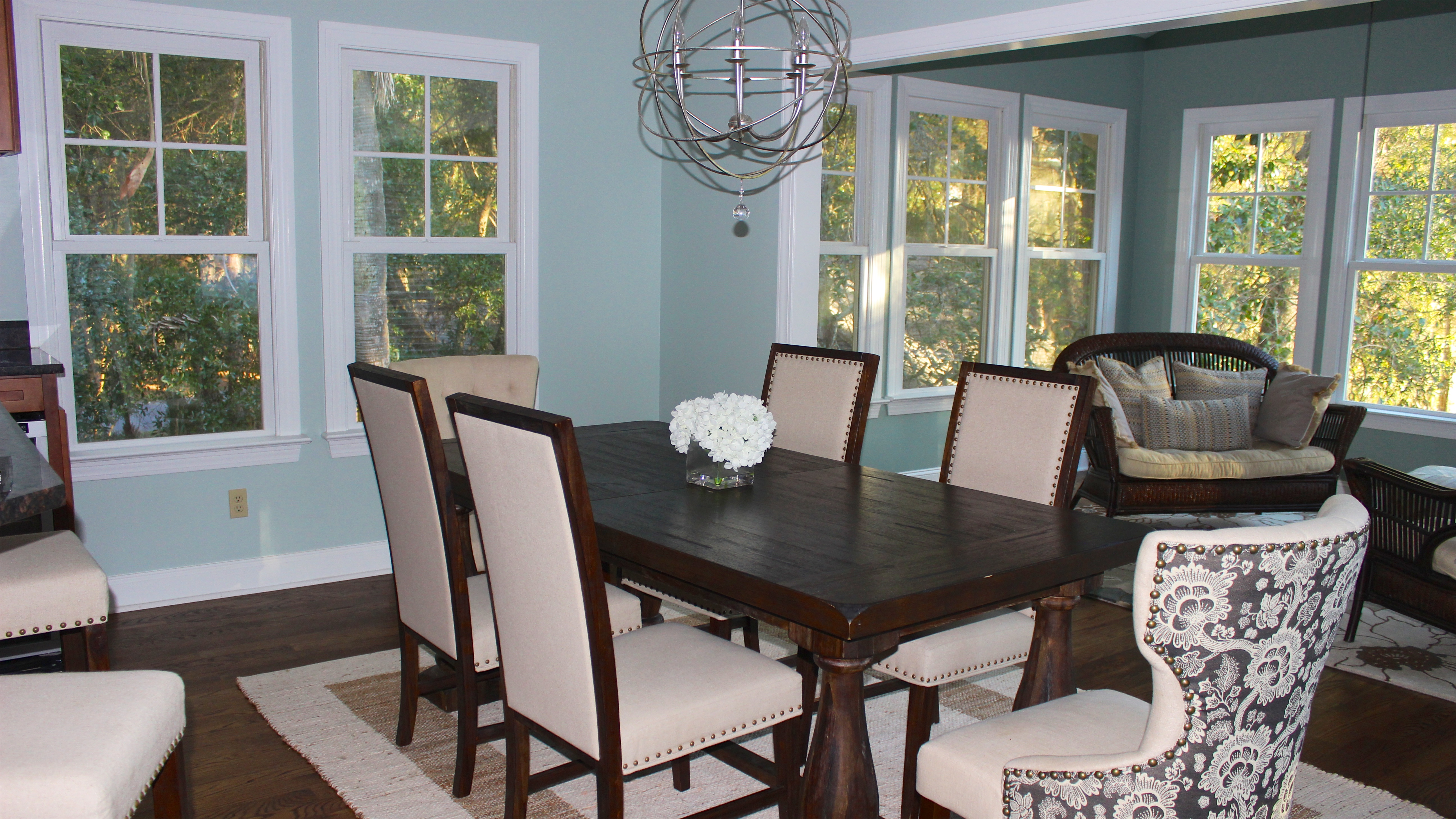The dining area has a table that seats 6 on upholstered chairs.