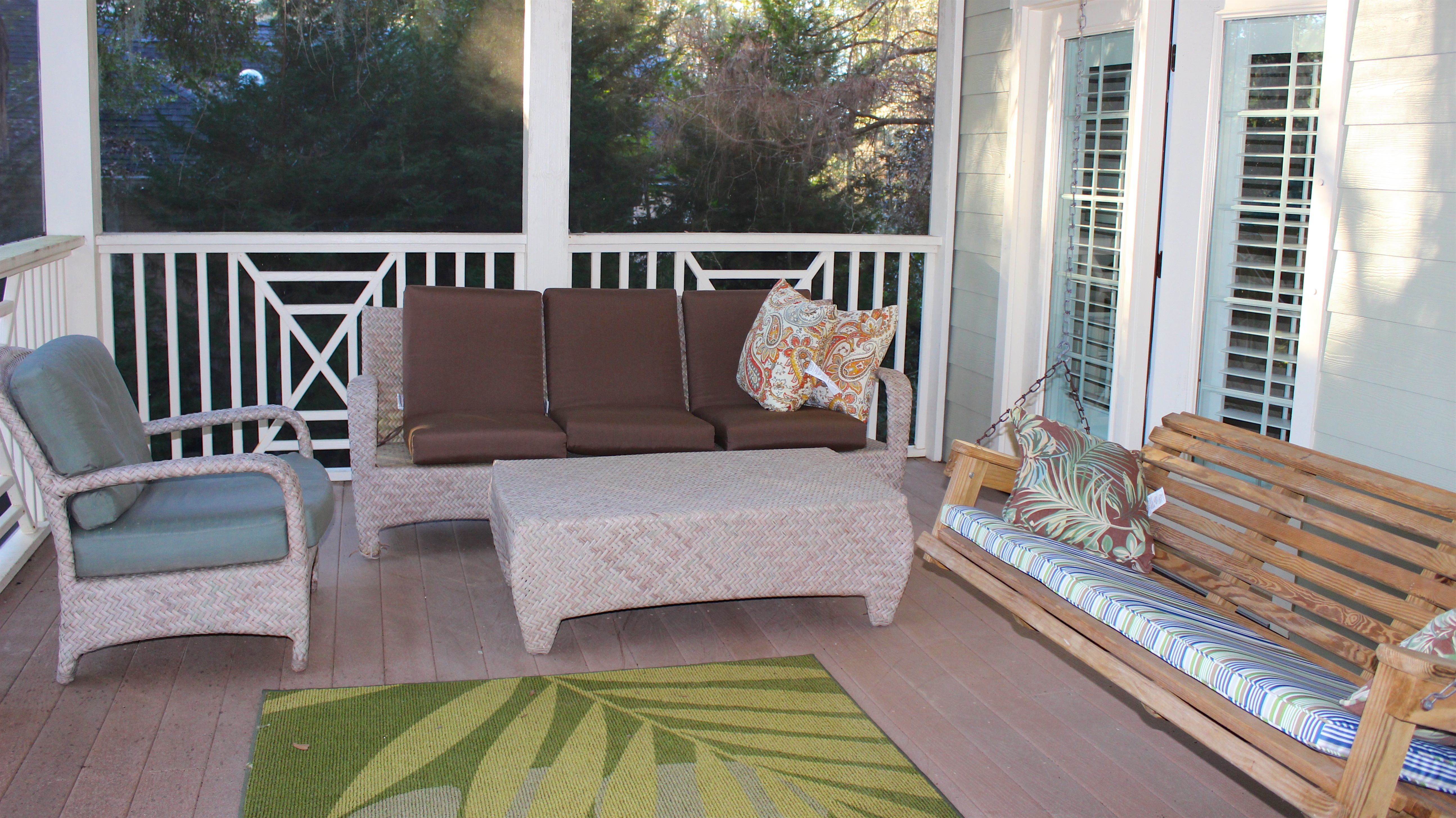 The screened porch has a seating area with a porch swing.