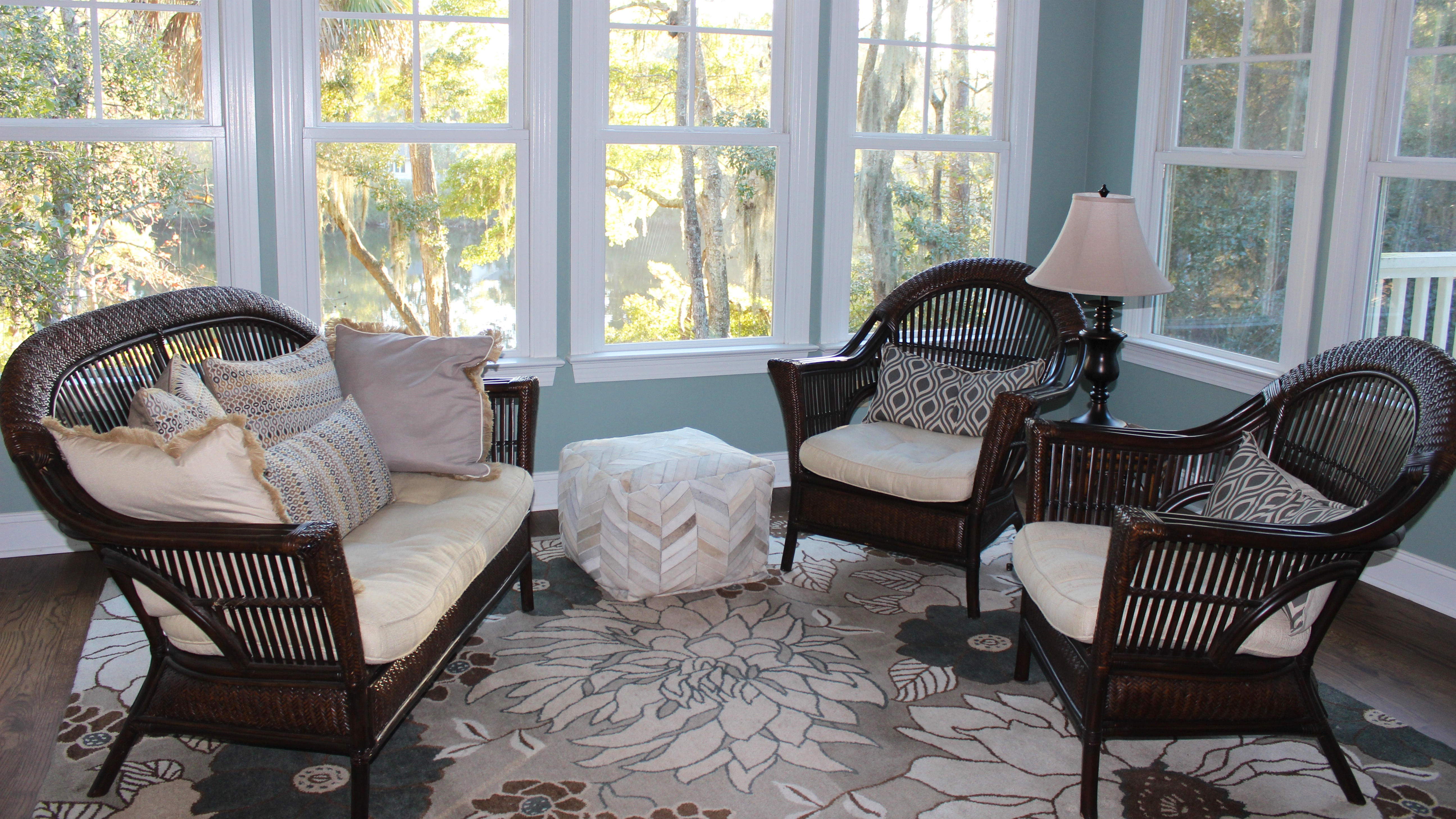 The sunroom is lined with windows offering views of the woods and lake beyond.