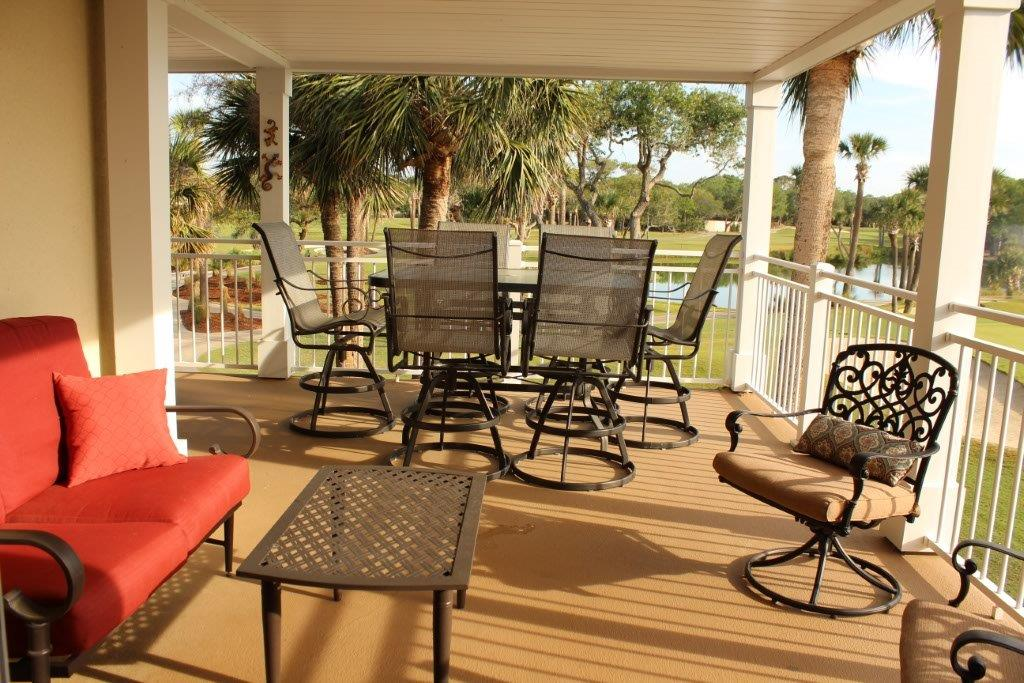 2903 patio with bar height dining table set (swivel stools) for six and separate swivel seating for two.        One of 4 golf course lagoons visible through railing.