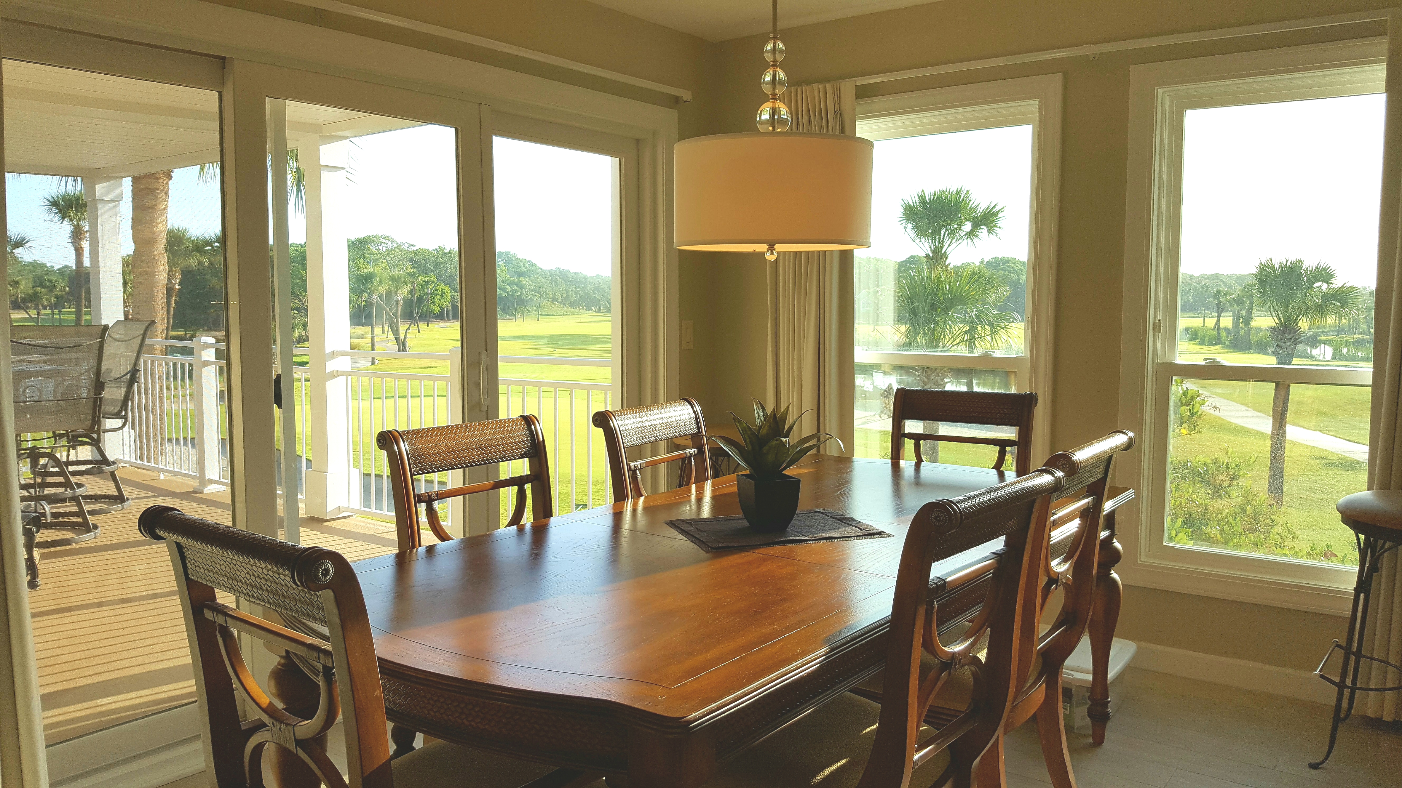 Dining table/chairs & down light pendant; breathtaking golf course panorama through windows and sliding door.
