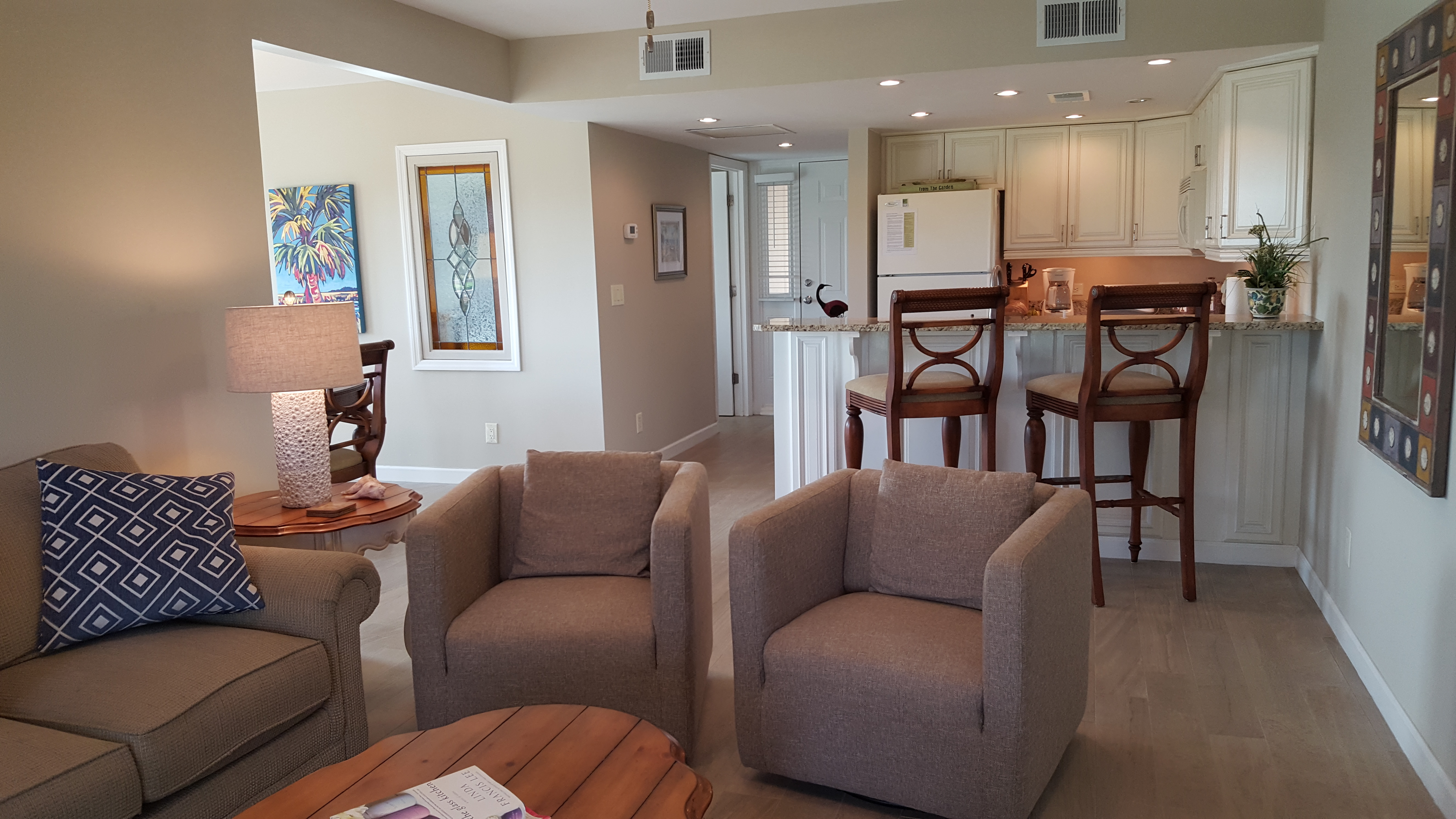 Living room seating group towards kitchen, breakfast counter, and entry hall.