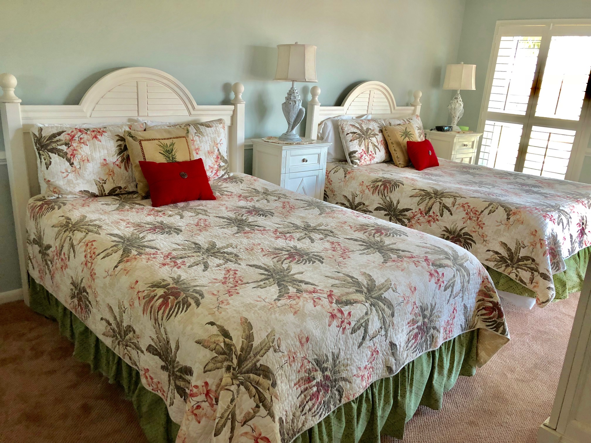 The 1st bedroom has two queen beds, plantation shutters, and a tropical decor.