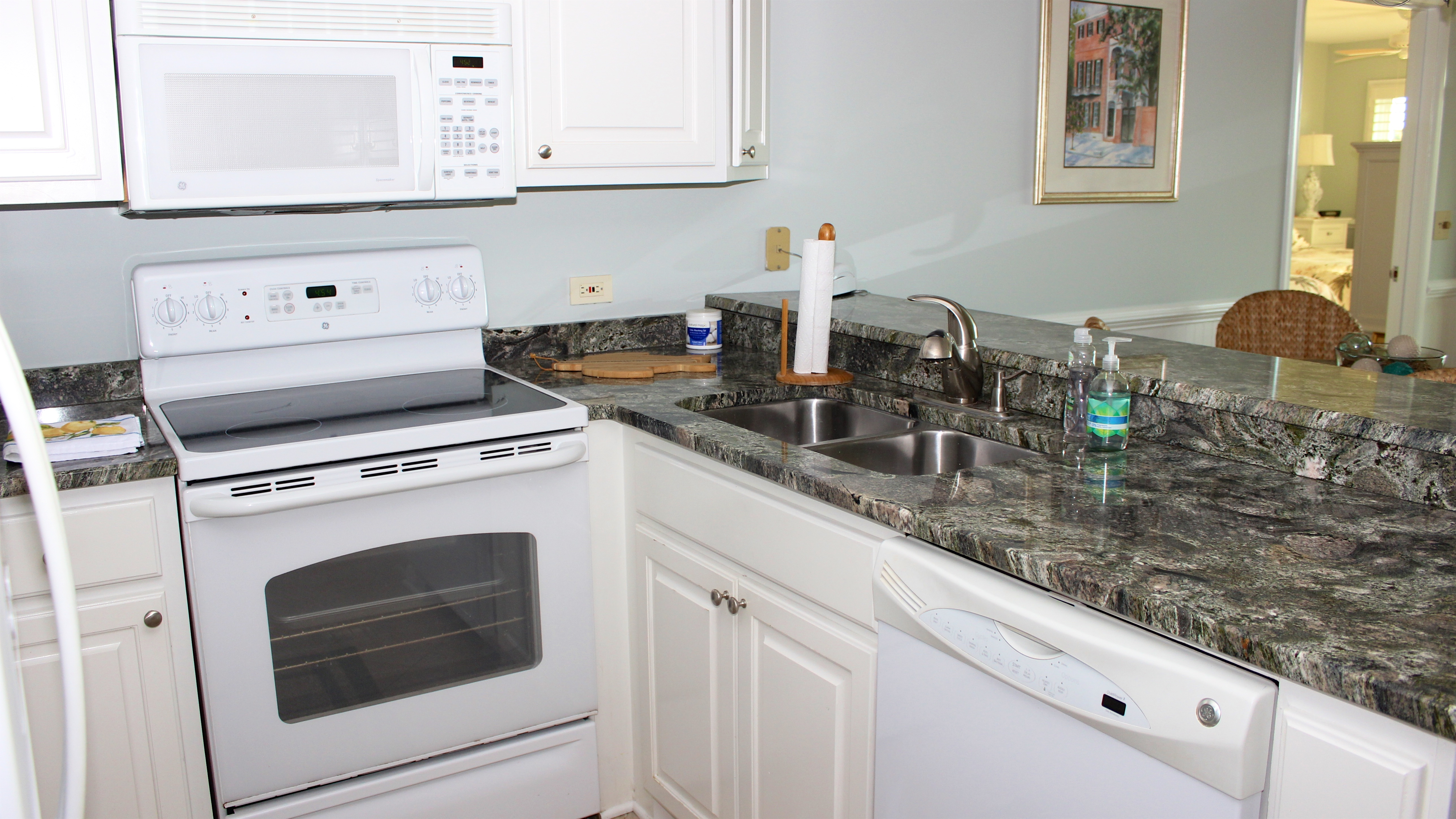 The soft green granite counters are a beautiful accent to the white cabinetry.