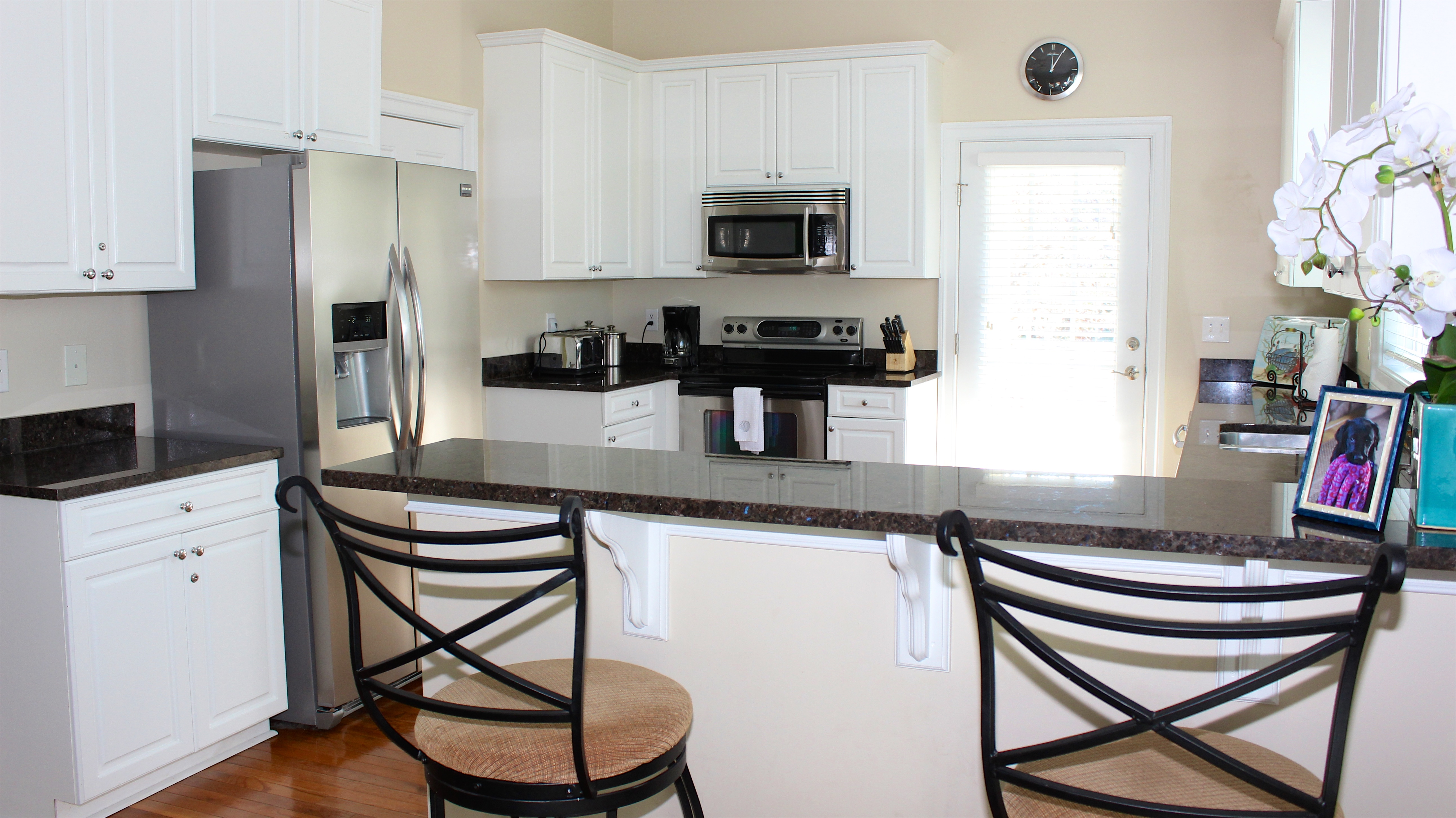 The kitchen features granite counters, custom cabinetry, and seating for 2.