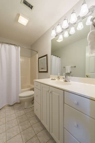 The hall bath has a tub/shower, tile flooring and a large vanity.