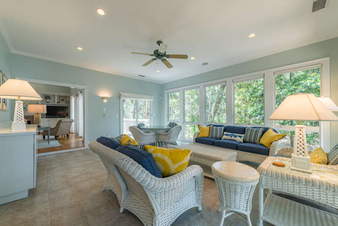 The sunroom has ample seating for gathering and dining.