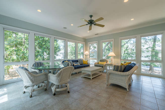 The sunroom has tile flooring & windows offering views of tropical landscaping.