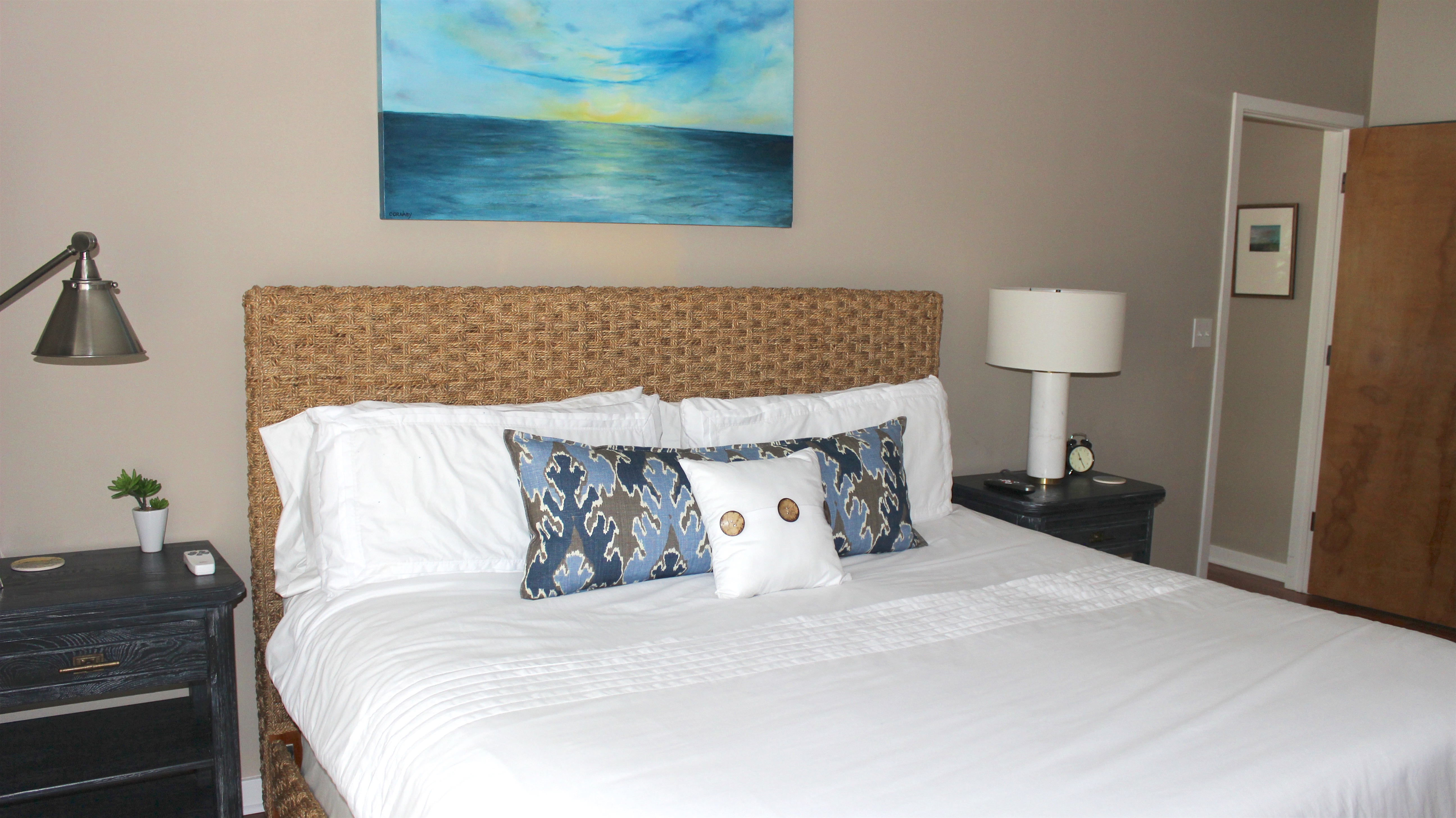 It has a king size bed with rattan headboard. Original art evokes beach dreams.